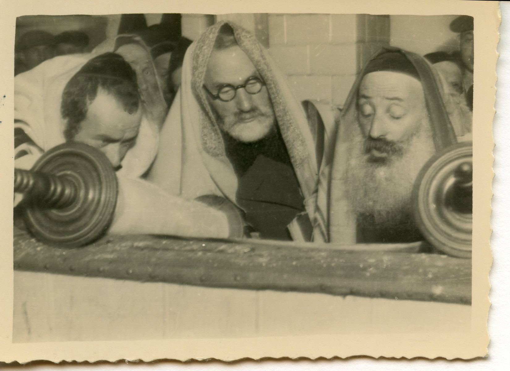 Three men read from a Torah scroll [perhaps in Osieciny].