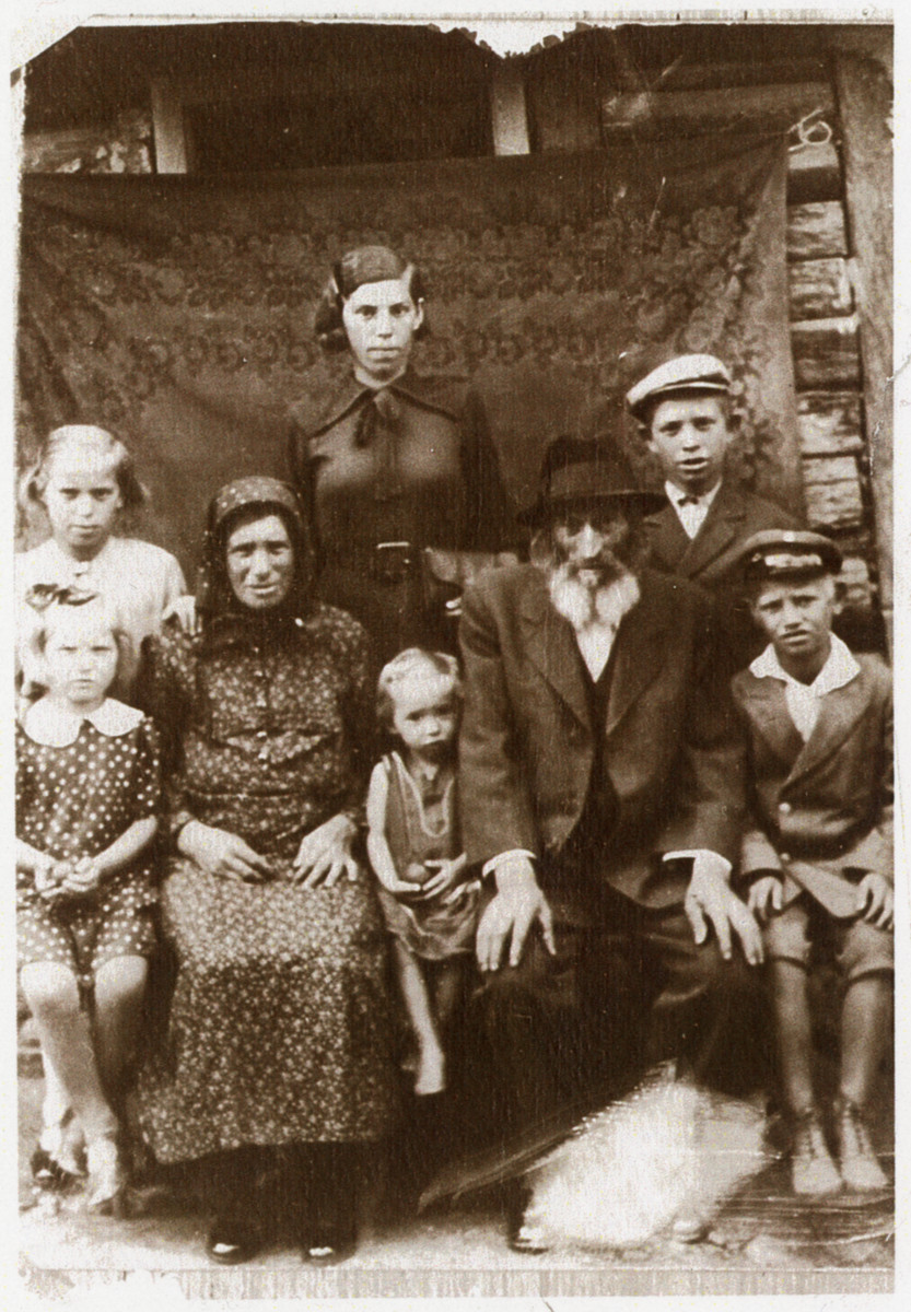 There Berkowitz family poses for a family portrait outside its's home.  Pictured seated left to right:  Mindya Berkowitz, Fradel Berkowitz, Chana Sura Berkowitz, Eliyah Berkowitz, Meyer Berkowitz.  Standing, left to right:  Rosie Berkowitz, Toby Berkowitz, Herschel Berkowitz.