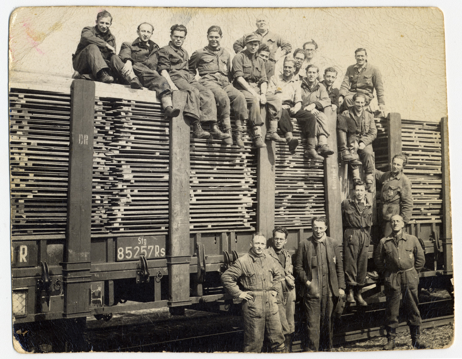 Jewish internees pose on top and next to a railcar loaded with planks of lumber in Westerbork.   Ignatz Kempler is standing at the base of train (second from right).