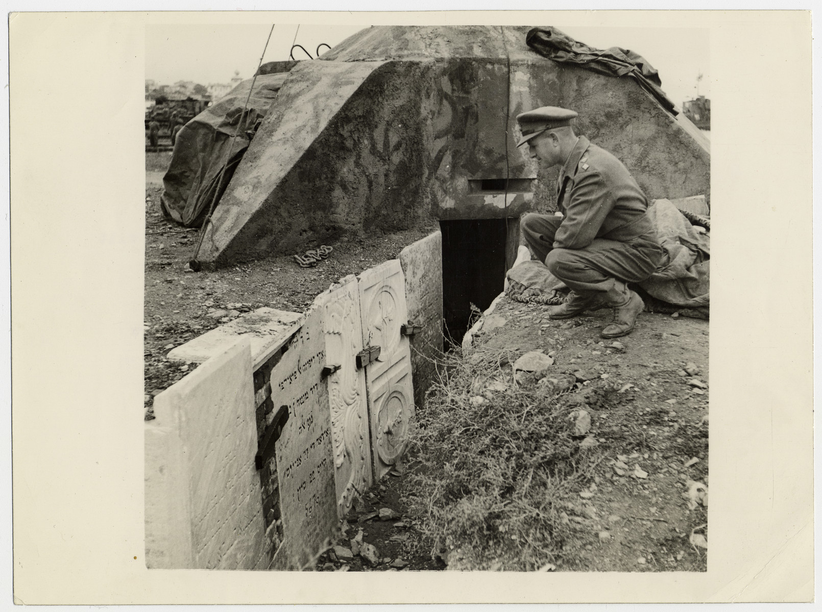 "Official British photograph showing a soldier staring at descrated Jewish tombstones in Salonika.   The official caption reads: ""Indian Units arrived by sea at Salonika on 11th Nov., 1944.  A German strongpoint, with slit trenches lined with tombstones from Jewish graves. In the background can be seen the concrete emplacement adjoining the slit trenches."""