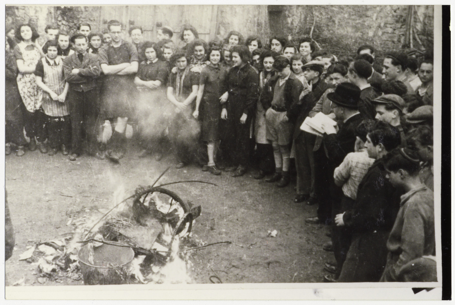 Jewish youth burn chametz [leavened bread] in preparation for the Passover holiday.  Among those pictured is Tosca Sussman in the back row.  Also pictured are Mary Auskerin, Arisch Schneider, Rabbi Sperber, Esther Weisner, Suzy Schindel, Erica Levin, Sonia Better, Tutti, Edith Metzger, Margot, David Graneck (work organizer), Annie Levin (nee Feldman), Lotte Aronowicz, and Ruth Ring (back center).