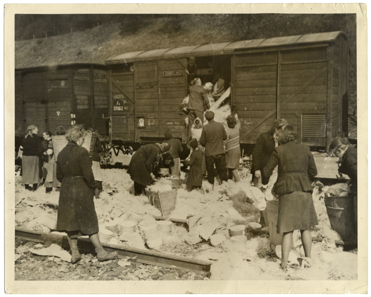 """German civilians loot a Nazi train as the war winds down.  Original caption reads: """"Civilians, mostly  women loot china from a Nazi freight car halted in railyards near Elsenoch, historic German town captured April 6, 1945, by troops of the Third U.S Army. Throughout  captured portions of the Reich, the fleeing of Gestapo members is the signal for German civilians, mostly women, to loot shops, trains, bombed houses and warehouses. U.S Signal Corps Photo ETC-HQ-45-61632"""""""