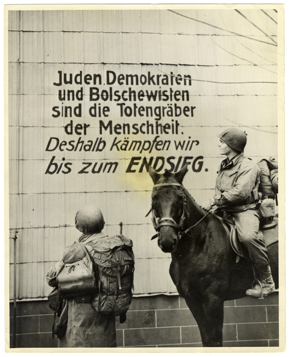 "U.S soldiers read Nazi propaganda written on a wall in France.  Original caption reads: ""Two U.S. soldiers read a German propaganda sign on a building in the Schirmock area of Alsace, Eastern France. The soldiers belong to an infantry regiment fighting on the Western Front. They carrry full field equipment and one of them rides  a horse abandoned by the Germans in their retreat. Schirmock lies in a valley in the Vosgoa Mountains, west of Molsheim on the road to Strasbourg. U.S. Signal Corps Photo MTO-HQ-44-20607"""