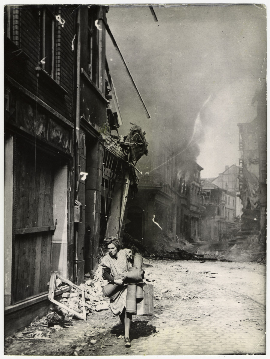 "A German woman flees a burning area in Sieburg.    The original caption reads: ""As a fire rages in the background, a German woman carries her belongings from a burning building on newly captured Sieburg, five mile northeast of Bonn and the Rhine, on the south of the Ruhr pockets. U,S, Signal Corps Photo."""