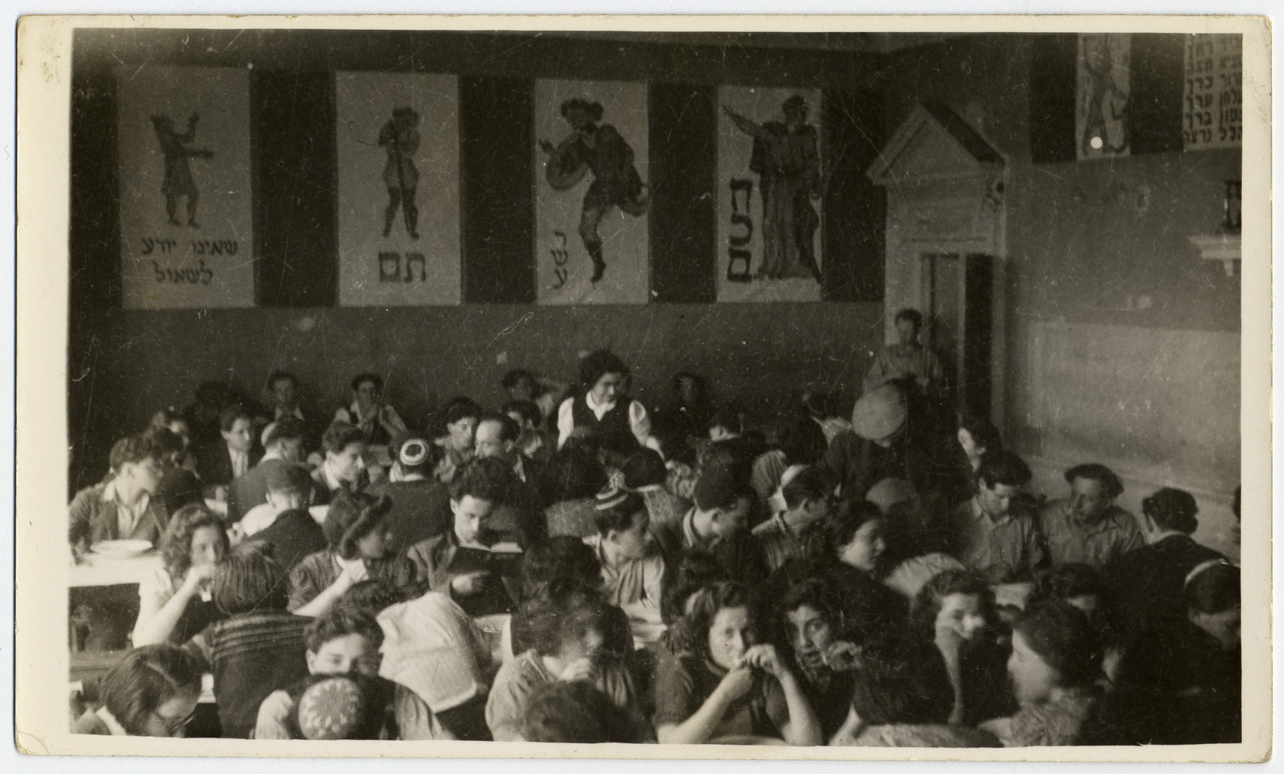 Jewish youth celebrate a model seder In Gwrich Castle.  Standing is Eva Carlebach.  To her left is Irving Seligman (head counselor).  Girl next to boy reading haggada is Bertel Karmiol.  Bottom left in glasses is Esther Graudenz.  Bottom center is Betti Einhorn and Bottom right are Edith Perlmutter, Bertel Rosenberg and Ruth Kessel.  In center, far right is Hersh Lerner.    The posters on the wall are four the four sons of the Passover haggadah.