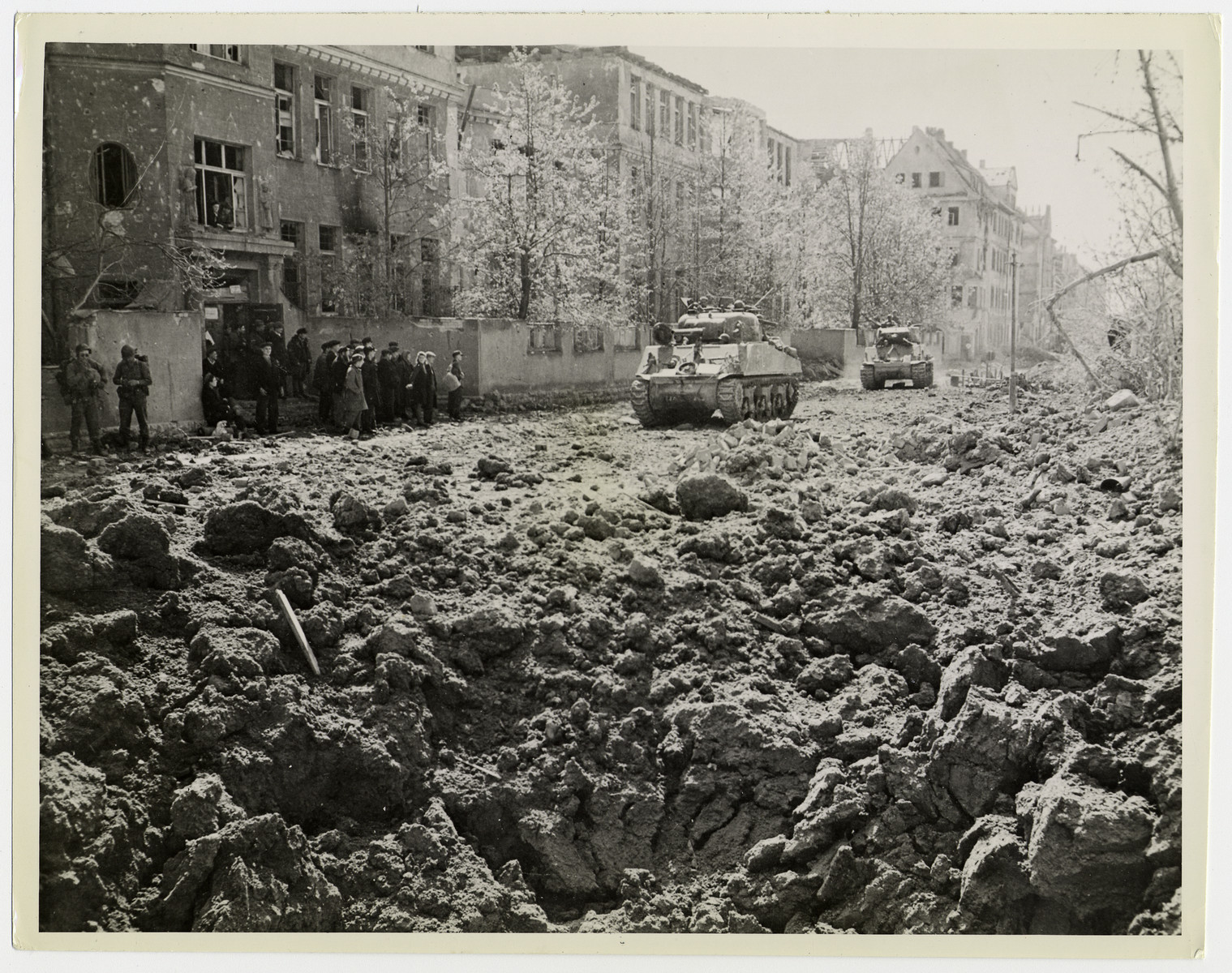 """U.S tanks advance through Schweinfurt.   Original caption reads: """"Liberated Russian victims of the Nazi forced labor system (left) watch as tanks of the 12th Armored Division, Seventh U.S. Army, rumble past shattered buildings in Schweinfurt, Germany.shortly after fall of the town April 11, 1945. Schweinfurt, heavily bombed and shelled before entry of Seventh Army ground forces, had been a main source of ball bearings for Nazi armament,. It is 86 miles east of the Rhine River and Mainz""""."""