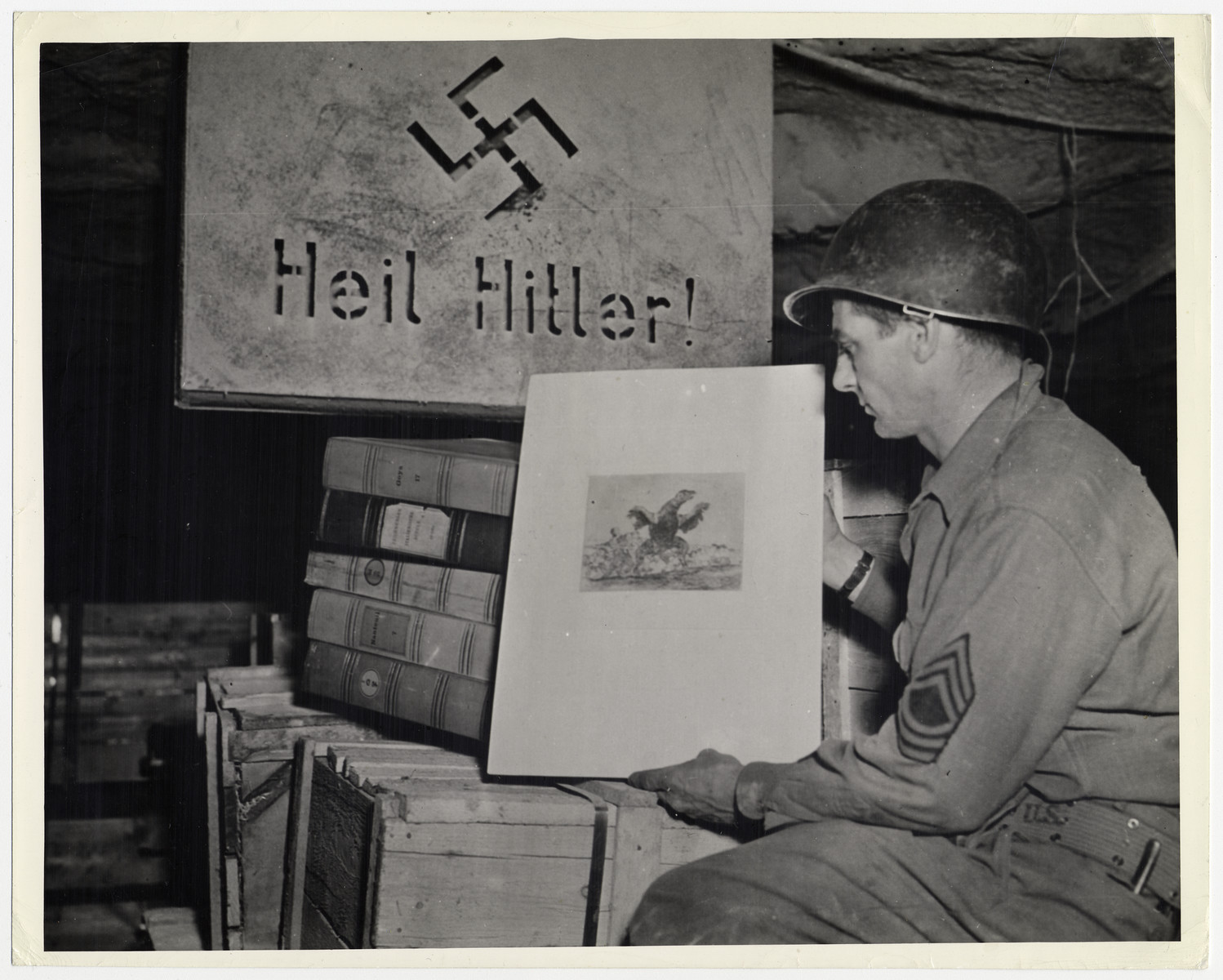 """Third U.S. Army discovers looted art treasures hidden by Nazis in a salt mine.    The original caption reads: """"Priceless art treasures and what is believed to be the entire gold reserve of the German Reichebank were discovered in a salt mine in Merkers,  Germany, by troops of the 90th Division, Third U.S. Army, April 7, 1946. The day after the capture of the mine, south of Mullhausen, Third Army engineers blasted a hole through a brick wall of an underground vault and found original paintings by Raphael, Rembrandt, Van Dyke and Durer as well as Goethe manuscripts.""""  THIS PHOTO SHOWS: Sergeant Harold Maus of Scranton, Pennsylvania, examines a painting by the 18th Century Spanish arist Goya, Above the art treasure is a stencil for Hitler signs, U. S. Signal Corps Photo ETO-HQ-45-32060."""