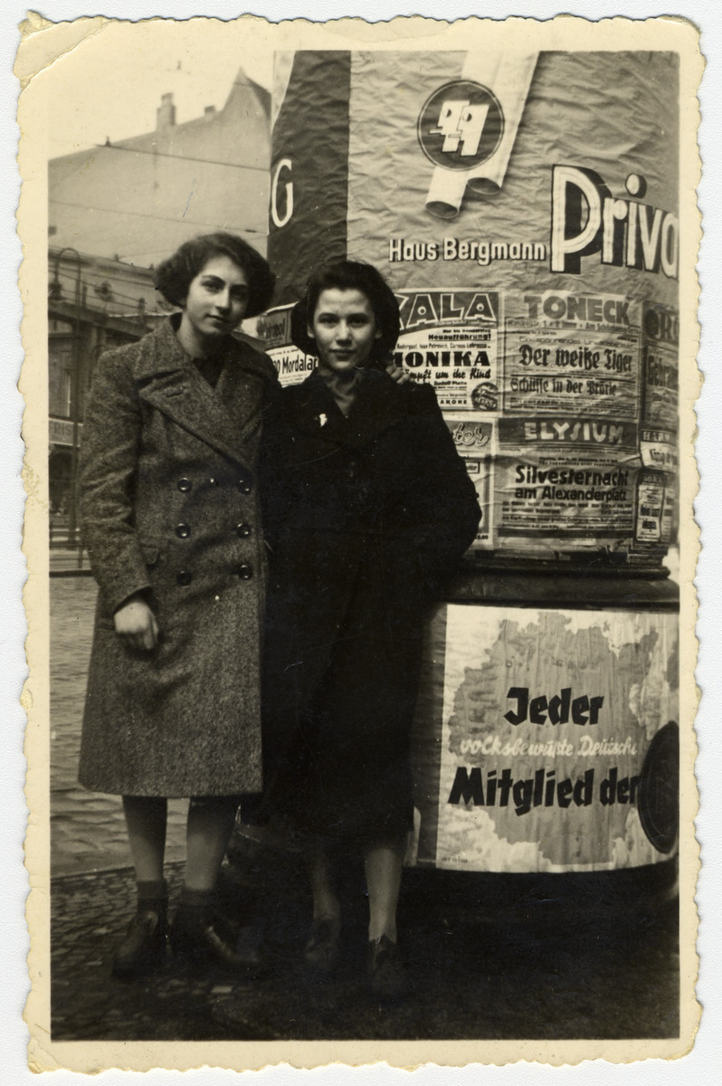 Rochen (Rosi) and Tosca stand in front of a pillar covered with posters and advertisements.