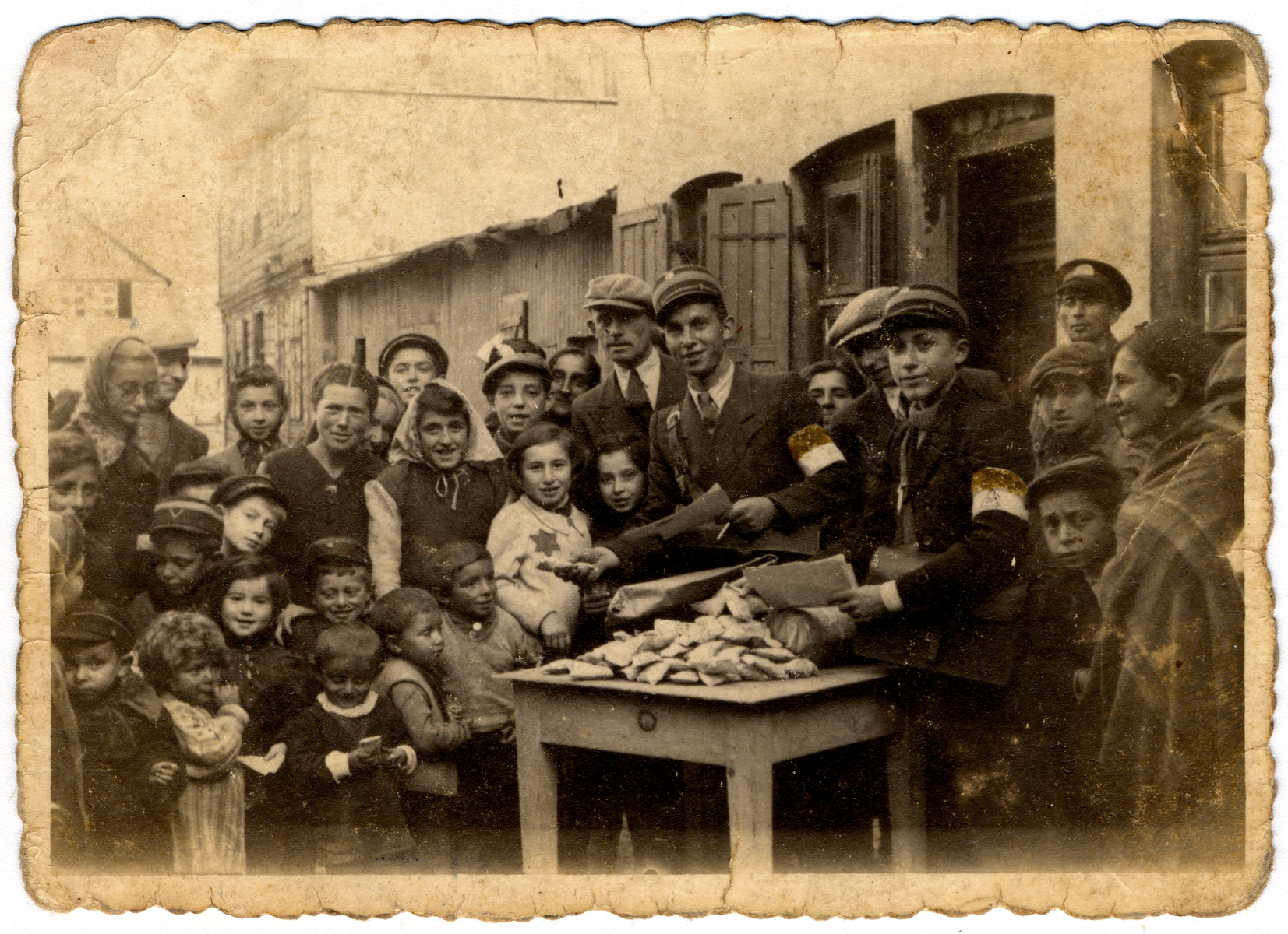"""J. Lewkowicz and A. Jakobowicz distribute candy for the holidays to the children in the Lodz ghetto.  [See #89759 for black/white version]  The original caption reads """"Memento for distribution of candy to children."""""""