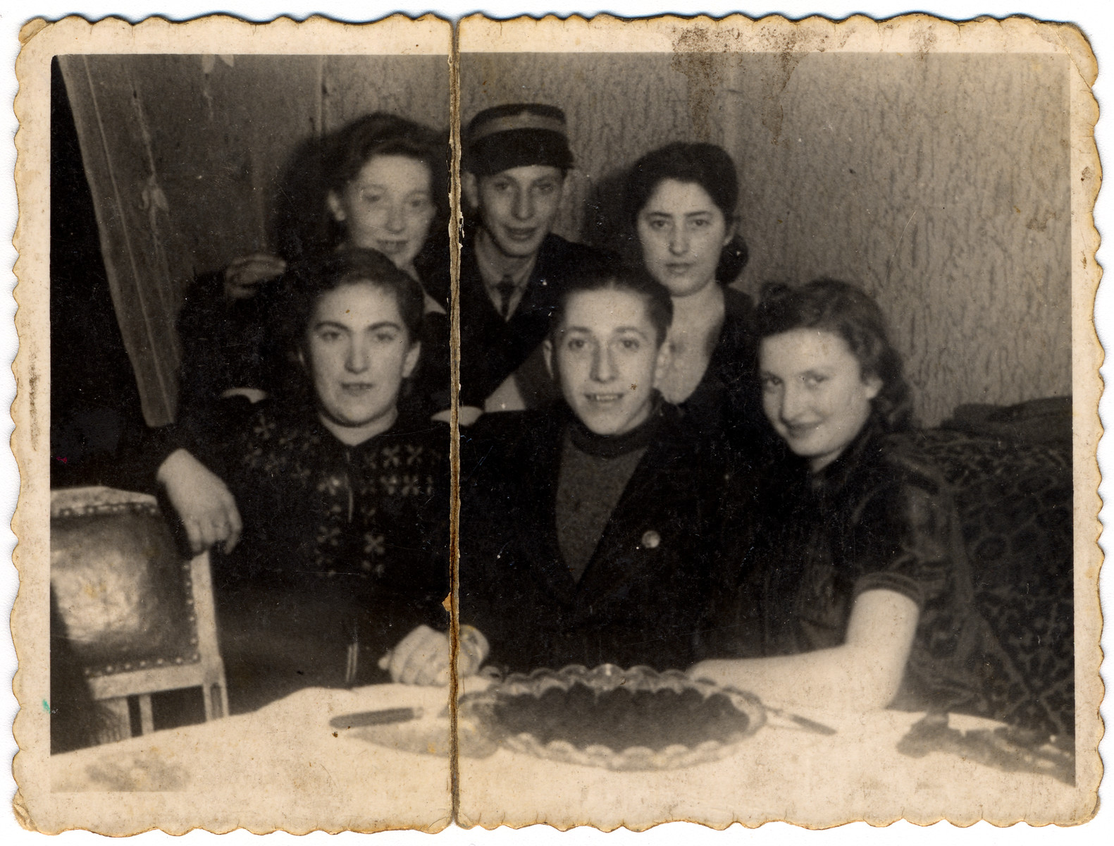 A group of four young girls and two boys (Jechiel and Izak Lewkowicz) pose at a dining-room table in the Lodz ghetto.   Izak Lewkowicz (standing second from left) is wearing his postal worker's cap. Jechiel is sitting in the center.