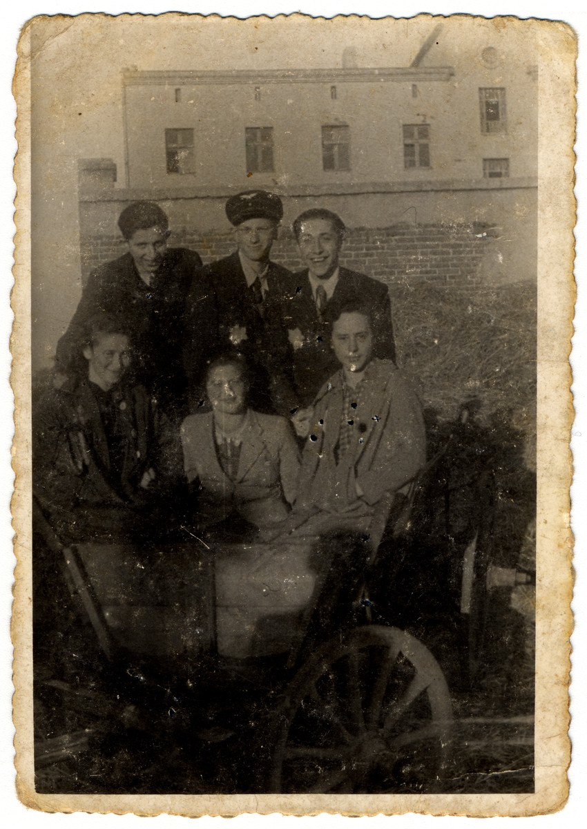 Group portrait of six young people, many wearing Jewish badges, in the Lodz ghetto.