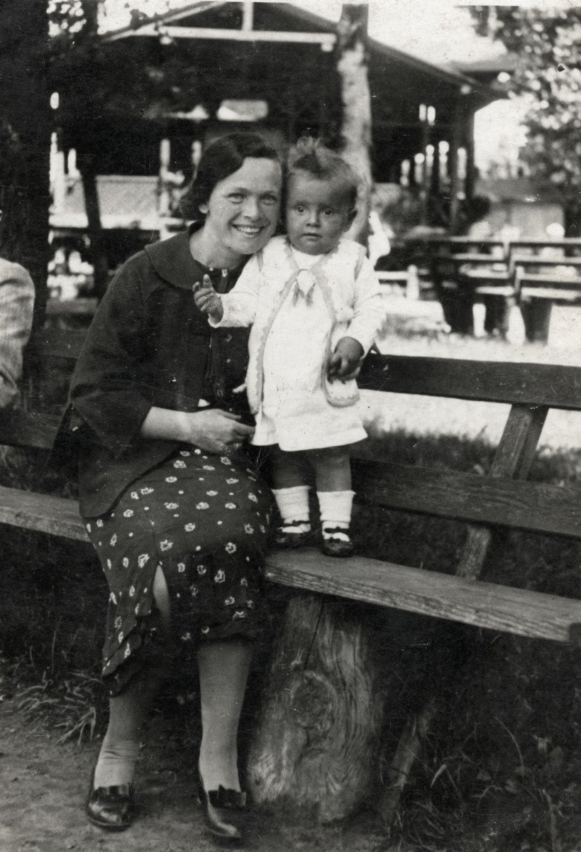 Sarah Korenzyer poses with her baby daughter Tsivia on a bark bench in Chelm, Poland.