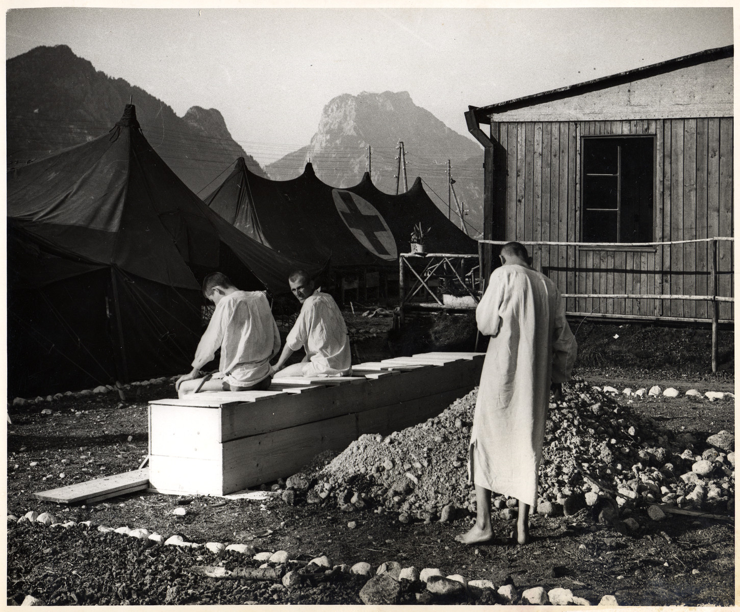 Survivors dressed in medical gowns use the latrines outside the Red Cross tent. in Ebensee