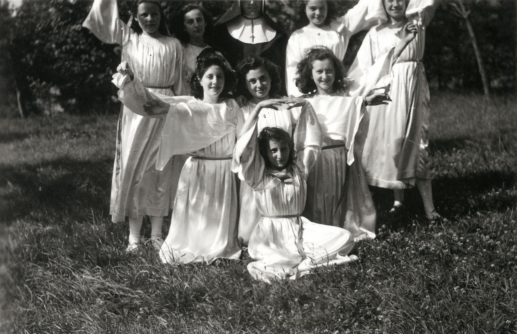 Group portrait of school girls, including Jewish girls in hiding, in the St. Antoine de Padue convent.  Liliane Ferdman is pictured in front with her hands above her head.
