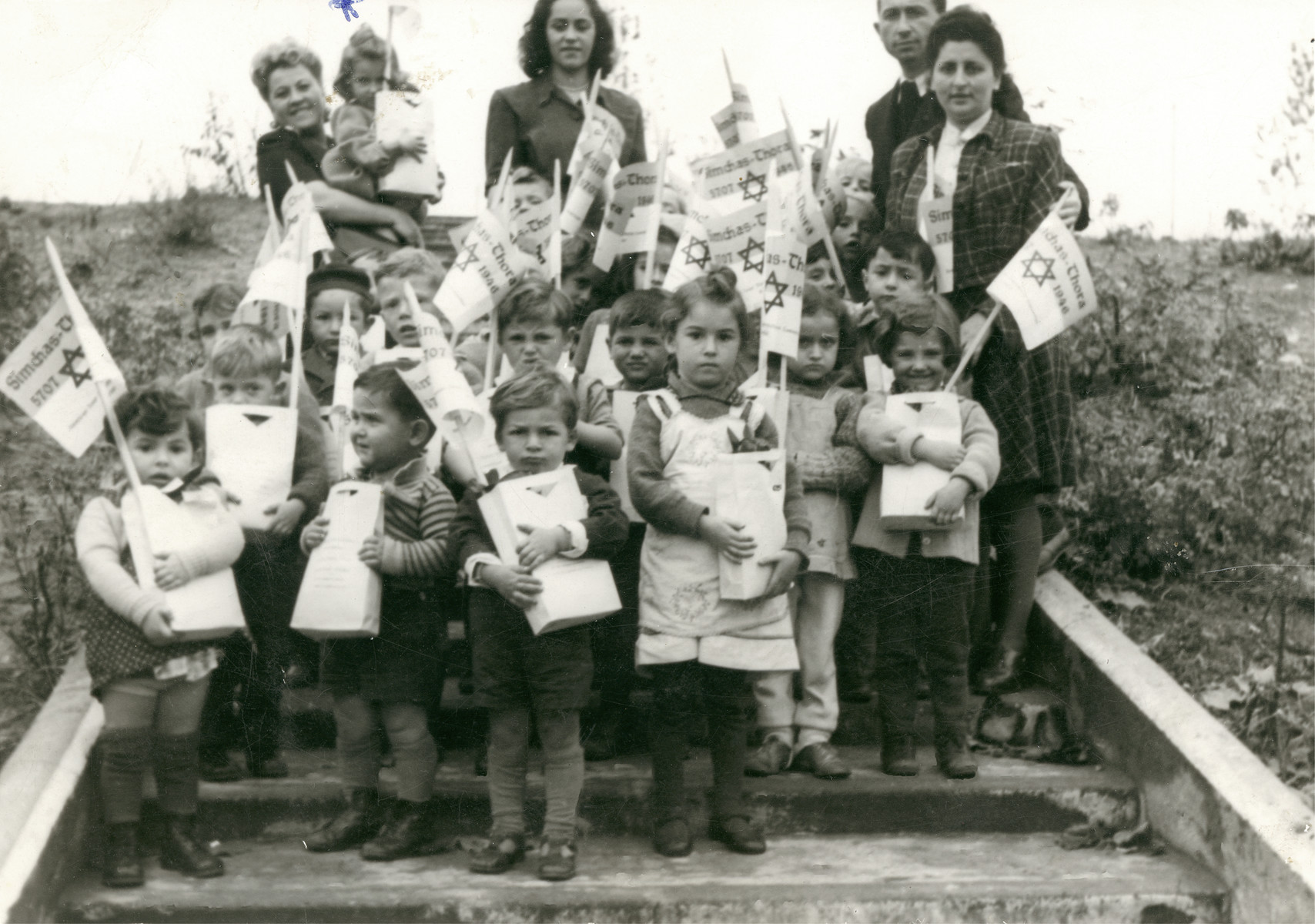 Young children carry small bags and flags during a Simchat Torah celebration in the Schlachtensee displaced persons camp.  Clara is the little girl being held by the woman on the far left, back row.