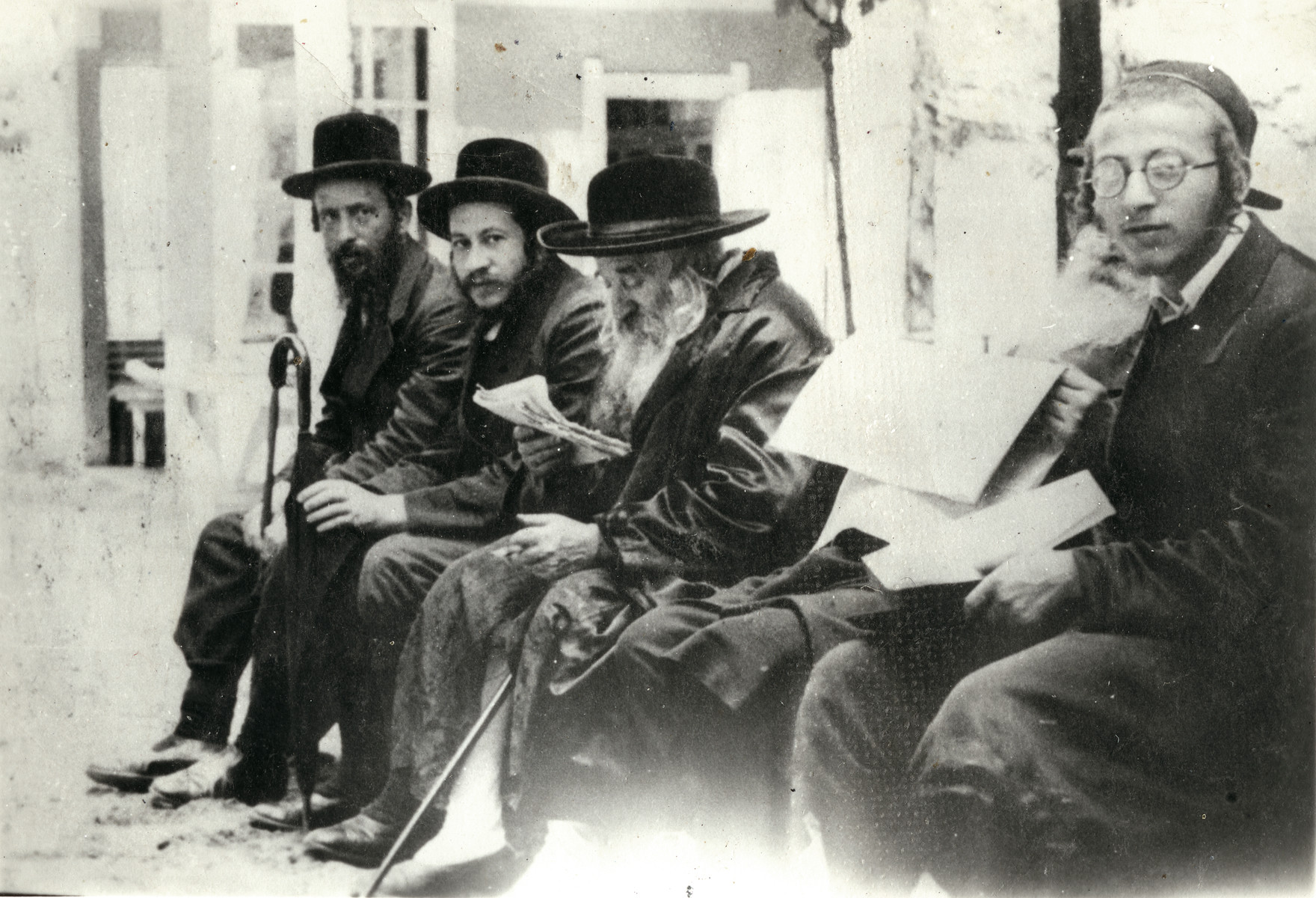 Group portrait of Hassidic Jewish men.  Chaim Braunfeld is pictured on the far left.  The Chernobler rebbe is second from the left and the Tchover Rabbi is third from the left.  Rabbi, Haim from Sanz and his grandson are on the right.