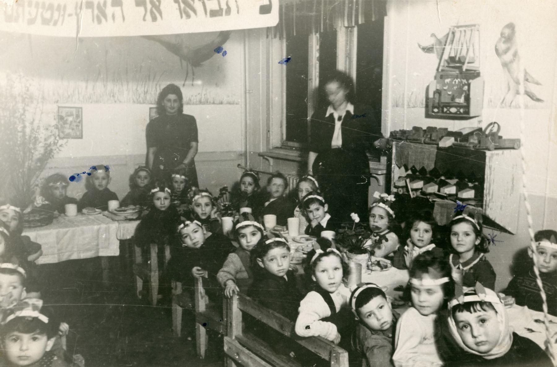 Kindergarten children celebrate Tu Bishvat in their class in the Schlachtensee displaced persons camp.