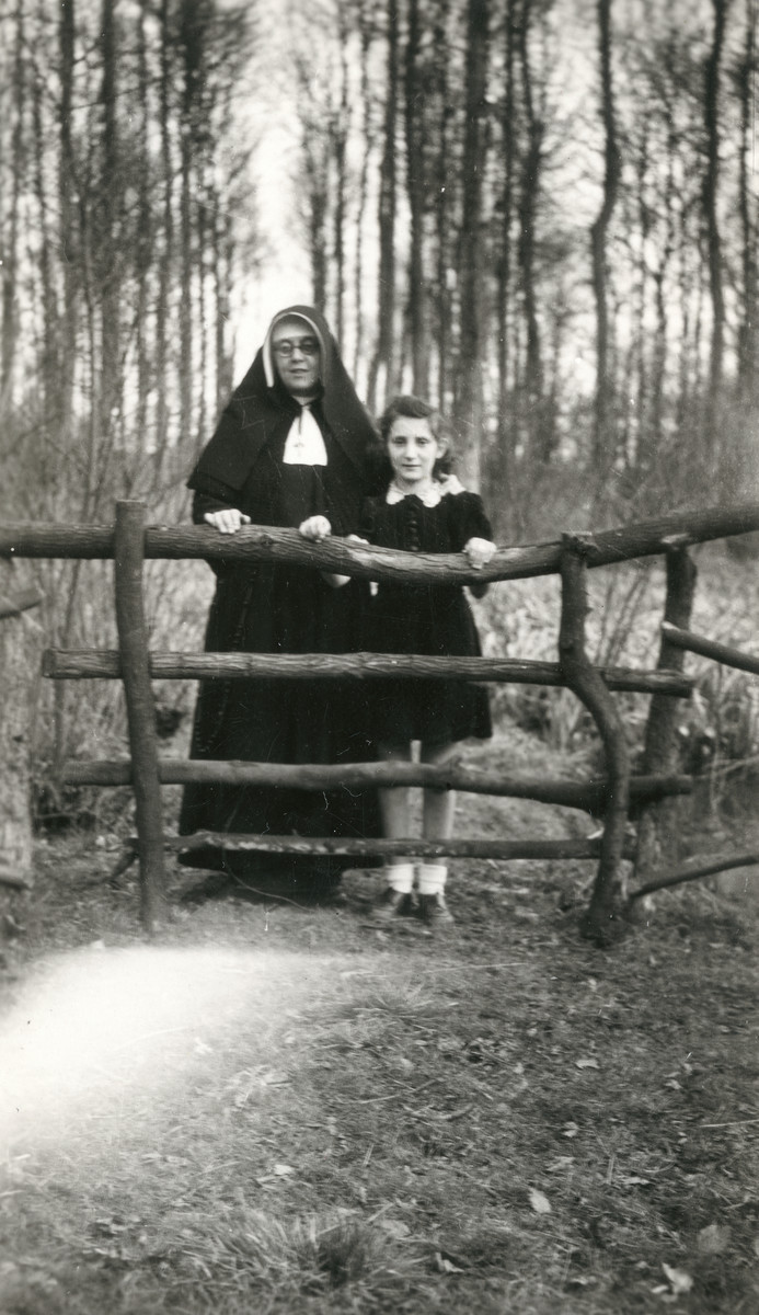 Liliane Ferdman, a Jewish girl in hiding, stands by a fence next to one of the nuns in the St. Antoine de Padue convent.
