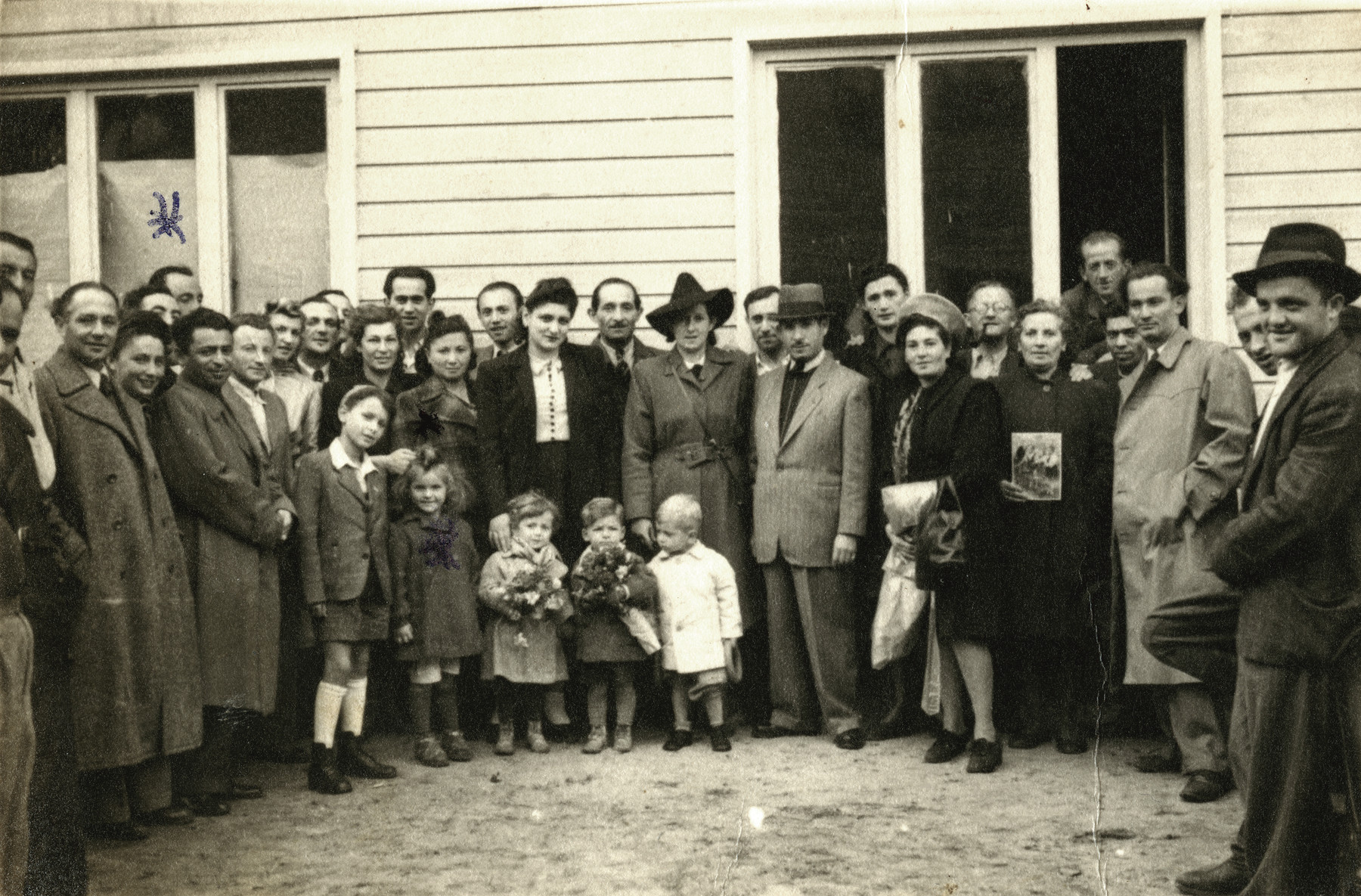 Group portrait of Jewish displaced persons in the  Schlachtensee camp.   Mosche Finkelstein is on the far left, last row. He is standing by the window and only half of his head is visible. His daughter, Clara, is the second child on the left, in the front row.