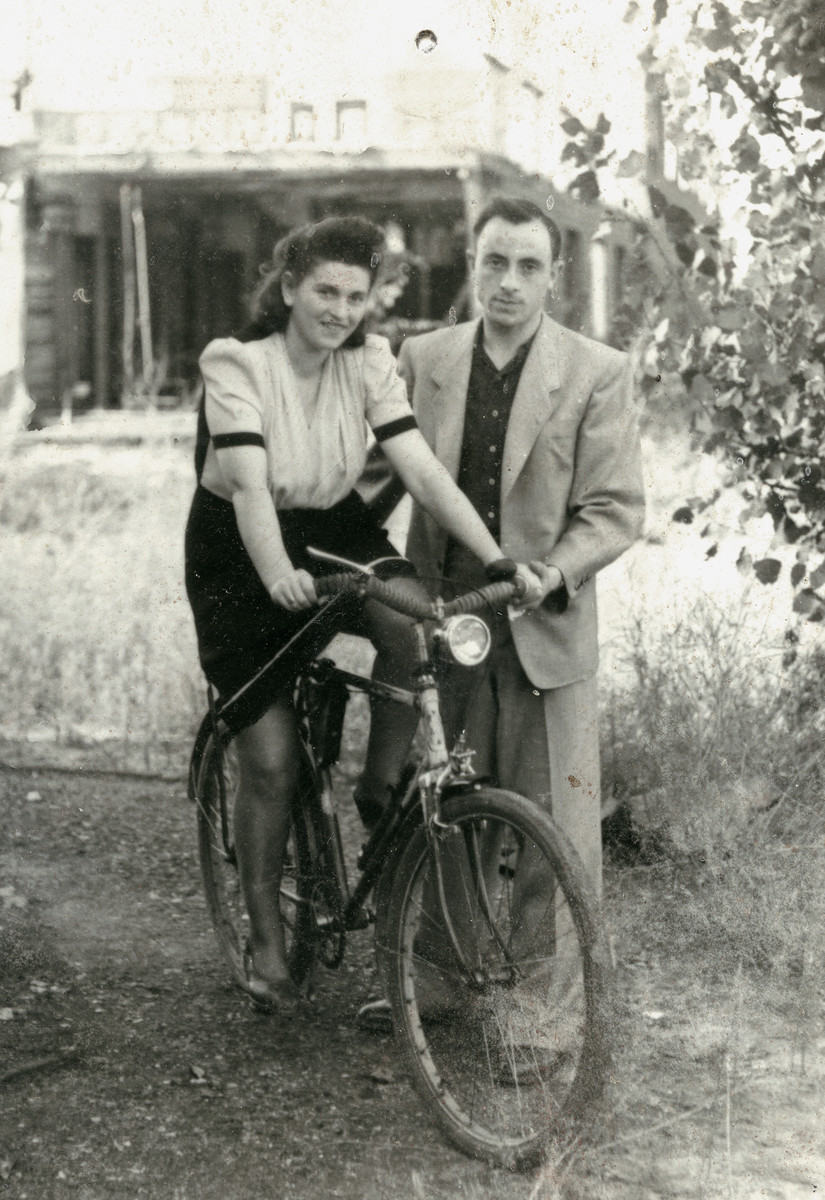 Frania (Freida) and Moshe (Moszek) Finkelstein pose with a bicycle in the  Schlachtensee displaced persons camp.