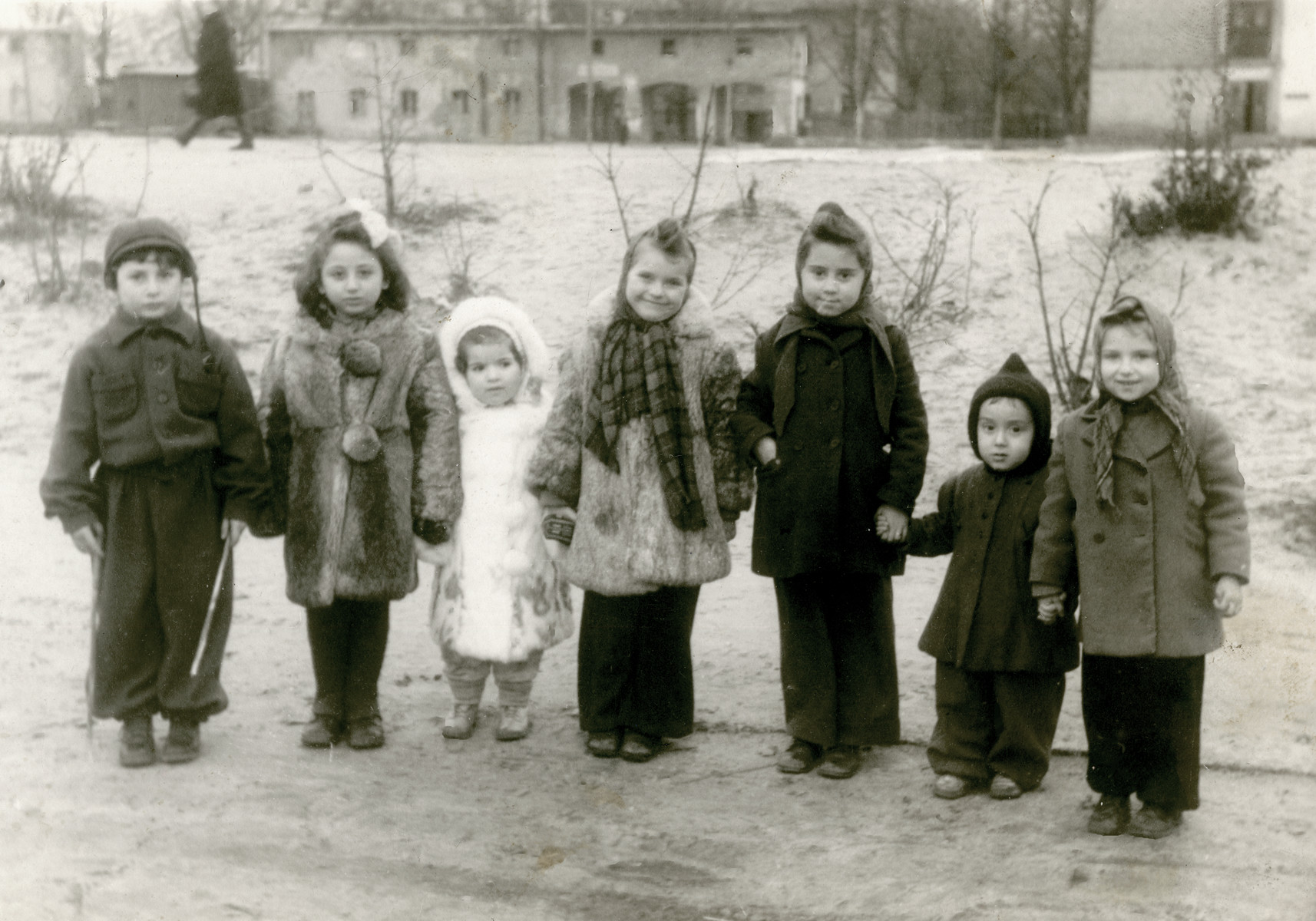 Clara stands outside with a group of young children in the Schlachtensee displaced persons camp  Clara is in the exact middle of the photo in a rabbit-fur coat.