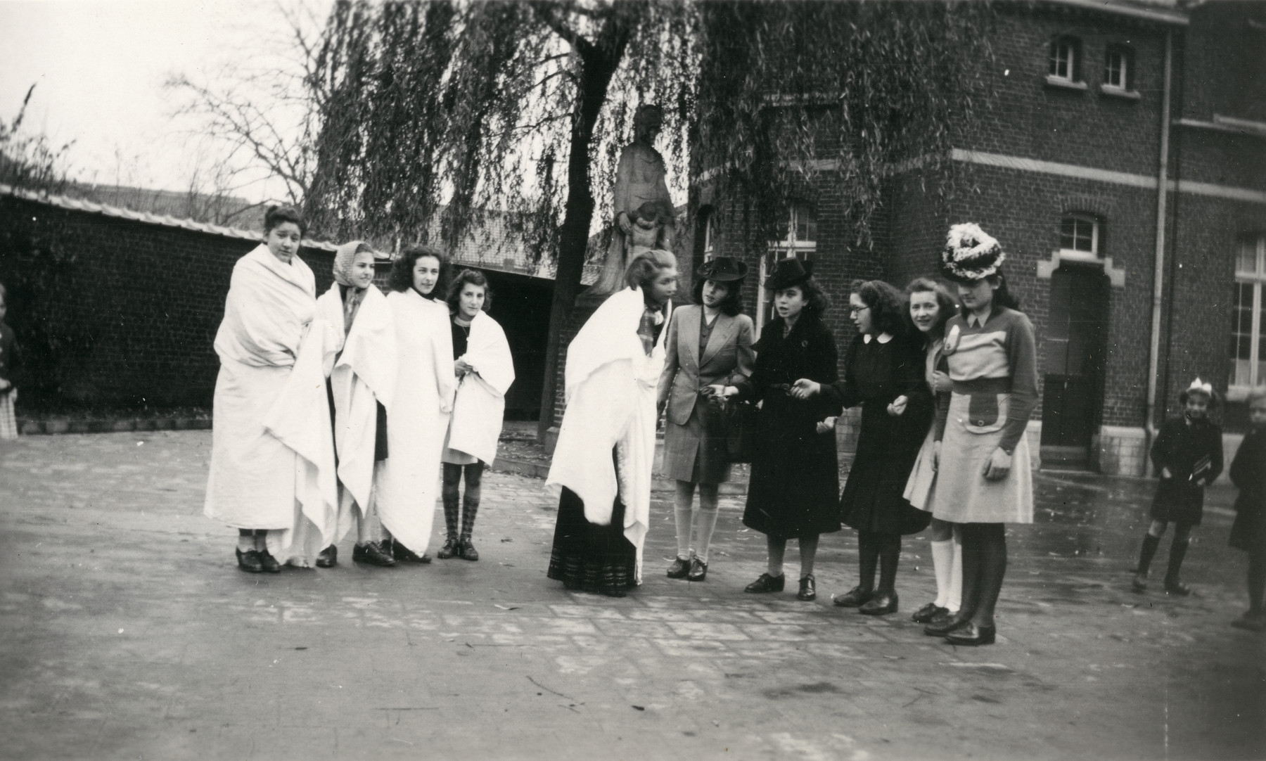 Teenage girls,many wearing costumes, gather in the courtyard of the Convent St. Antoine de Padue.   Liliane Ferdman is pictured fourth from left and her sister Suzie is second from right.