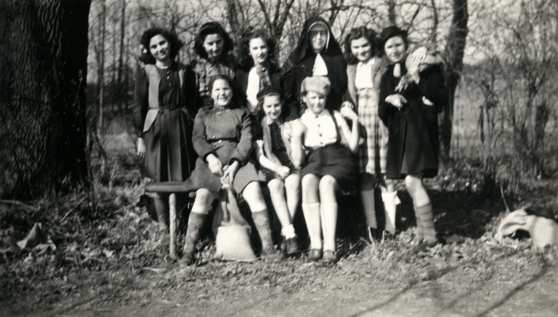 Group portrait of school girls, including Jewish girls in hiding, with a nun in the St. Antoine de Padue convent.  Liliane Ferdman is pictured  in front center wearing beret.