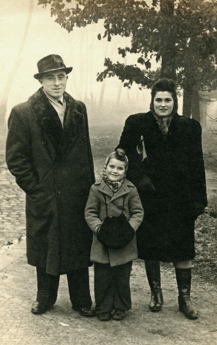 Clara stands outside with her father, Mosche (Moszek) and her mother, Frania (Freida) Finkelstein.