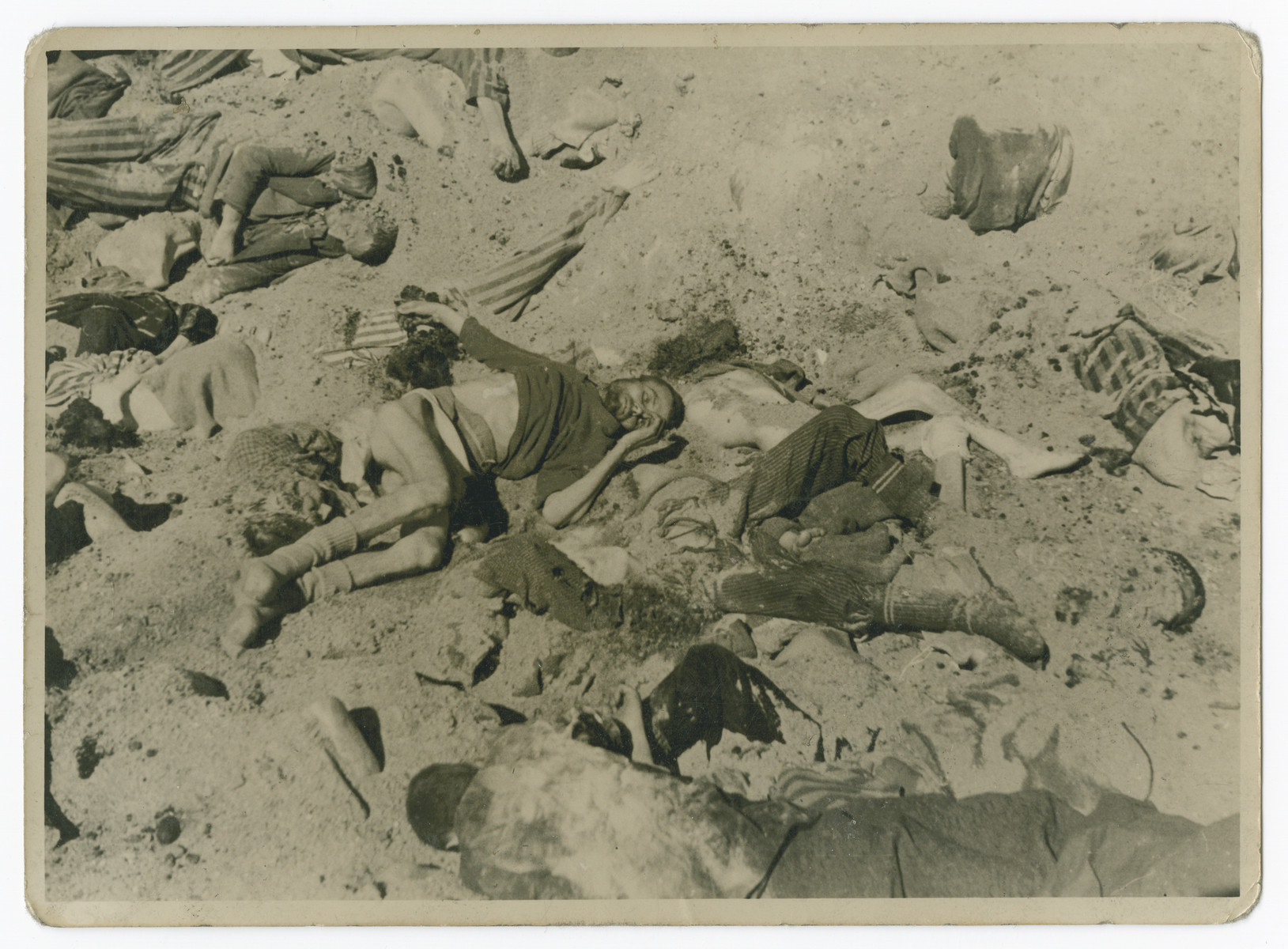 "Victims lie in a mass grave in the Bergen-Belsen concentration camp.  The original caption reads: ""One of the pits in Belsen."""