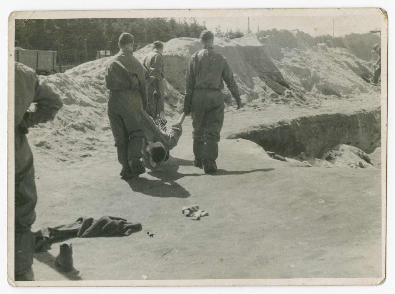 "Soldiers bury victims in a large pit in the Bergen-Belsen concentration camp following liberation.  The original caption reads: ""From truck to pit at Belsen."""