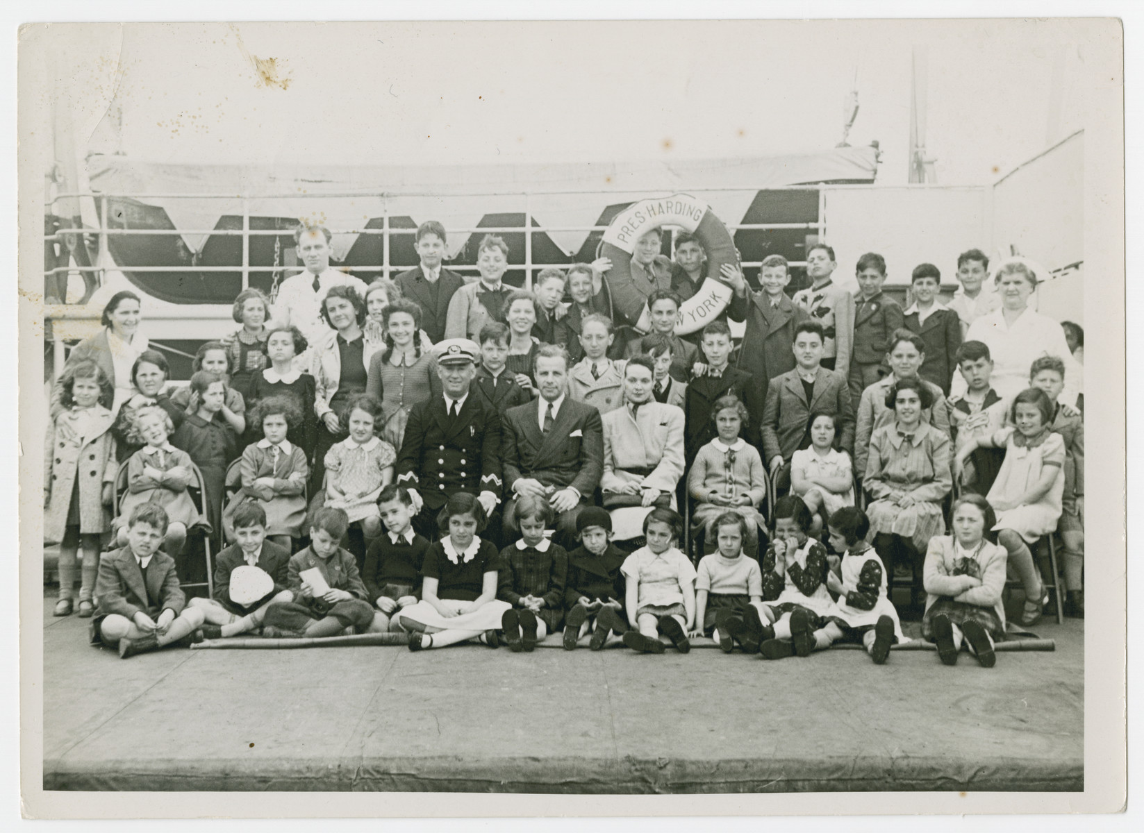 Gilbert and Eleanor Kraus (center) pose with the fifty Austrian Jewish children they are bringing to the United States.  Johanna and Robert Braun are standing directly behind the Captain and Gilbert Kraus.