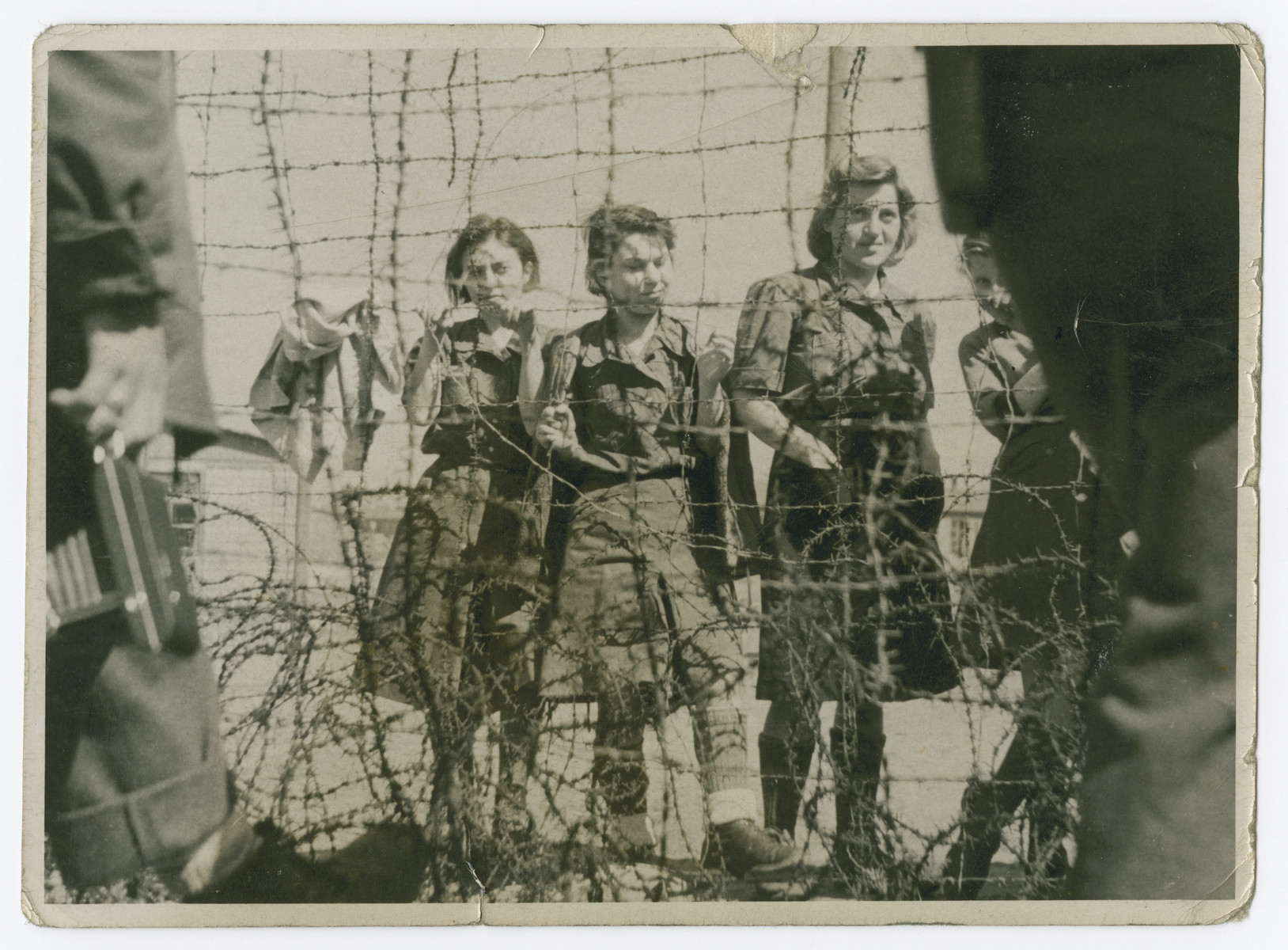 "Captured female guards stand behind a barbed wire fence in the Bergen-Belsen concentration camp.  The original caption reads: ""Some of the SS girls at Belsen."""