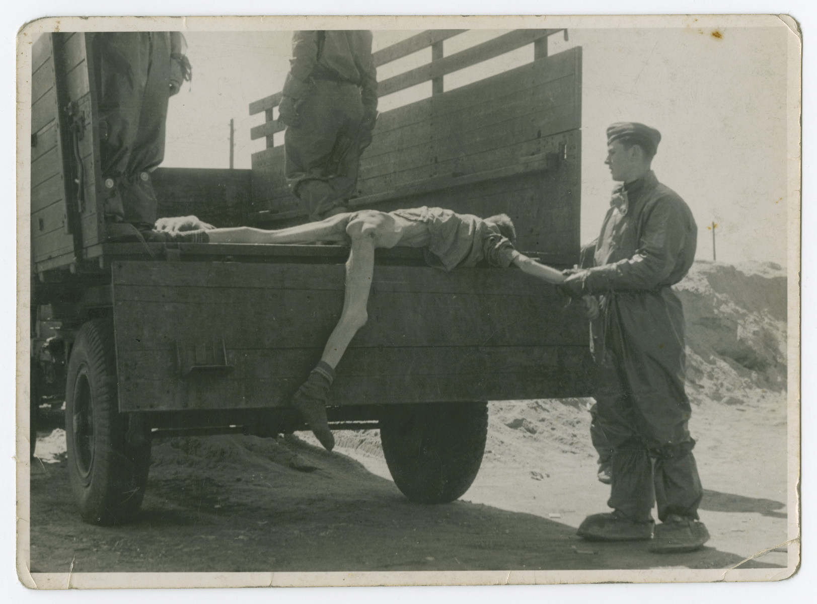 "Soldiers load corpses onto trucks prior to the their burial.  The original caption reads: ""Loading another bunch of stiffs in the truck for the pit in Bensen."""