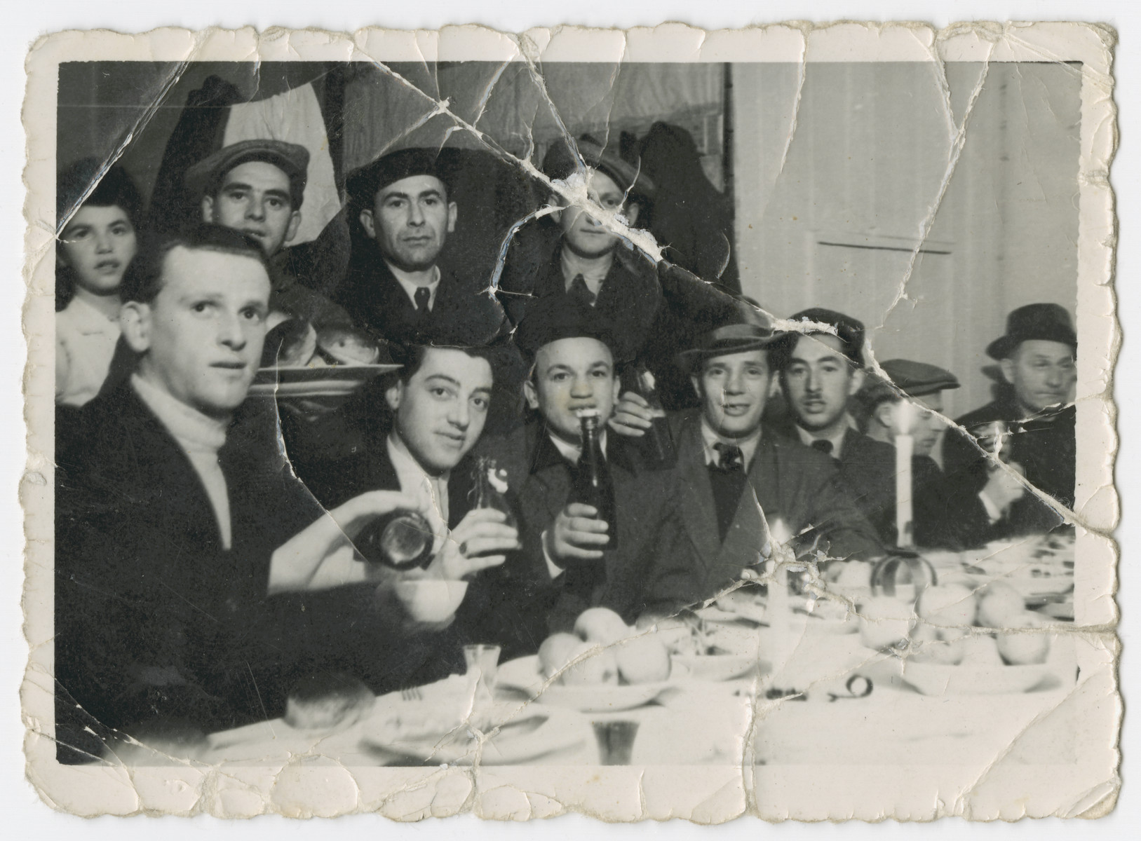 A group of men and women gather for a festive meal in the Bergen-Belsen displaced persons camp.  Among those pictured are David and Anna Rosenzweig, and their cousins Ben and Joe Rosenzweig.