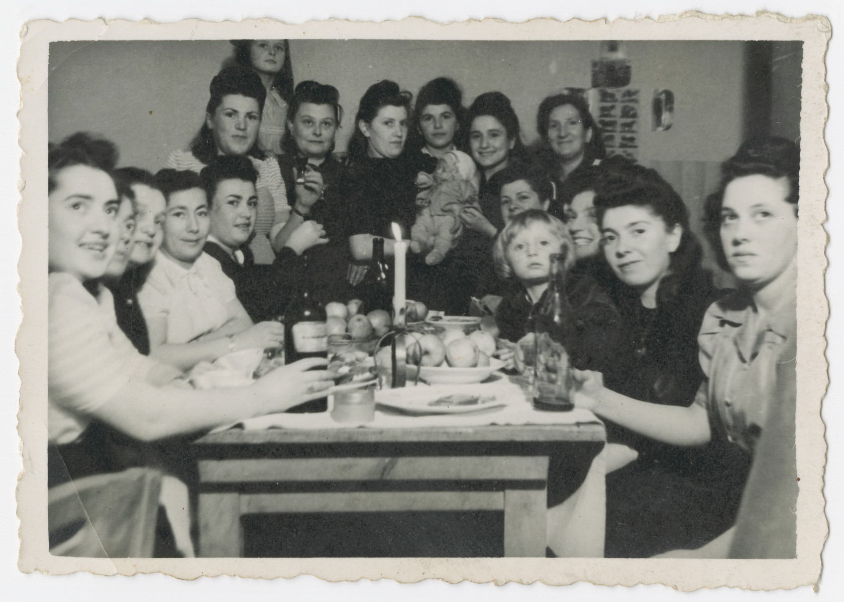 A group of women gather for a festive meal in the Bergen-Belsen displaced persons camp.  Anna Rosenzweig is in the rear, and her sister-in-law Mary Sadie Rosenzweig is on the far right.