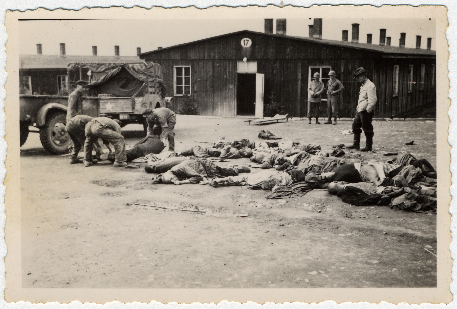 Survivors of Buchenwald clear corpses from the road in front of Barracks #17, as some American soldiers look on.