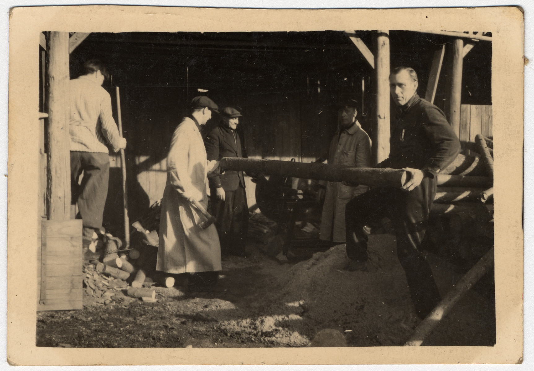 "A group of men work in a lumber workshop, perhaps affiliated with a sanatorium.  The original Czech caption reads, ""As a memento from Sanatorium, Buda and Zasmok."""