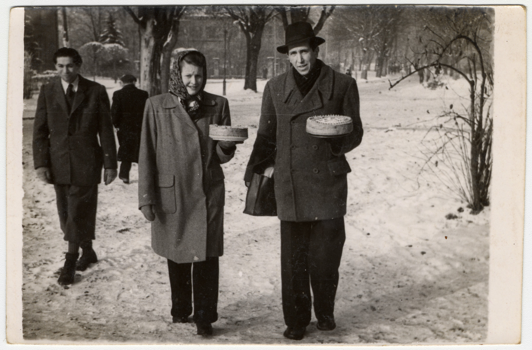 A man and woman walk through the Gabersee displaced persons camp carrying cakes.