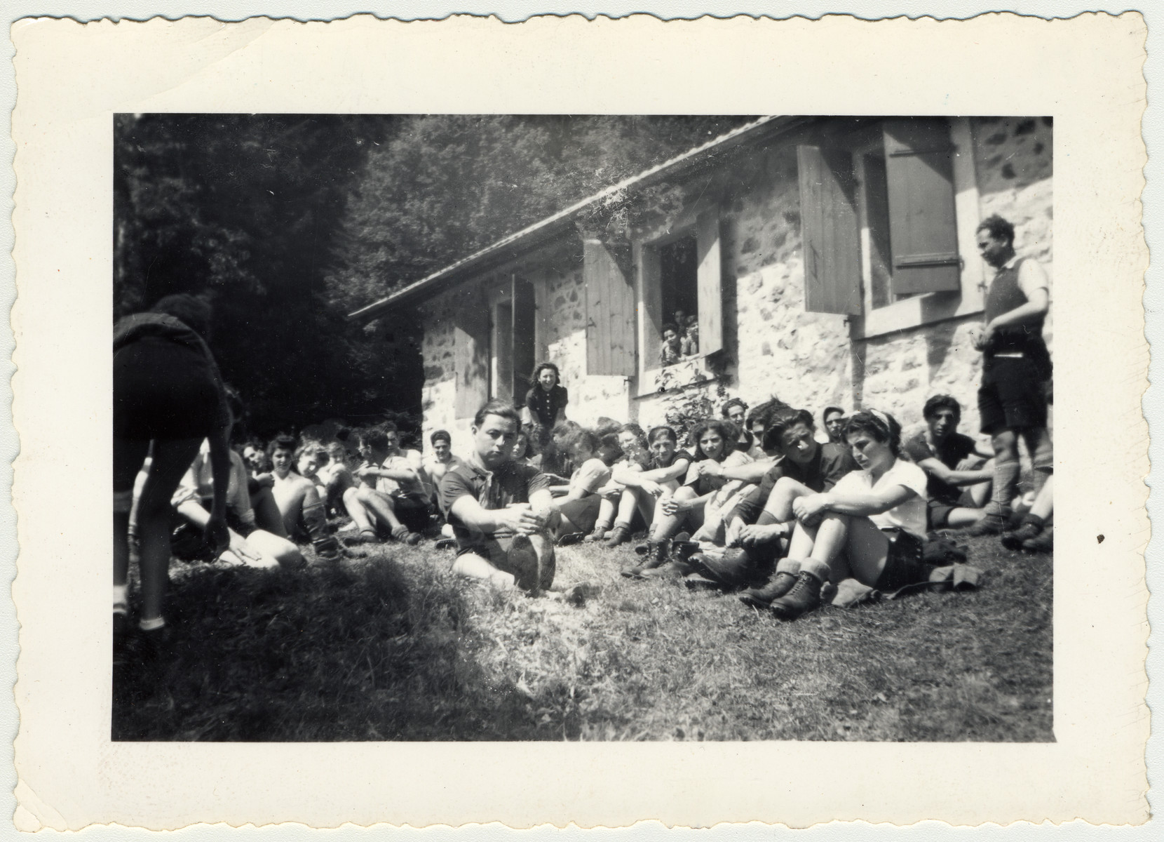 Zionist youth sit in the grass at their summer camp for a group discussion.