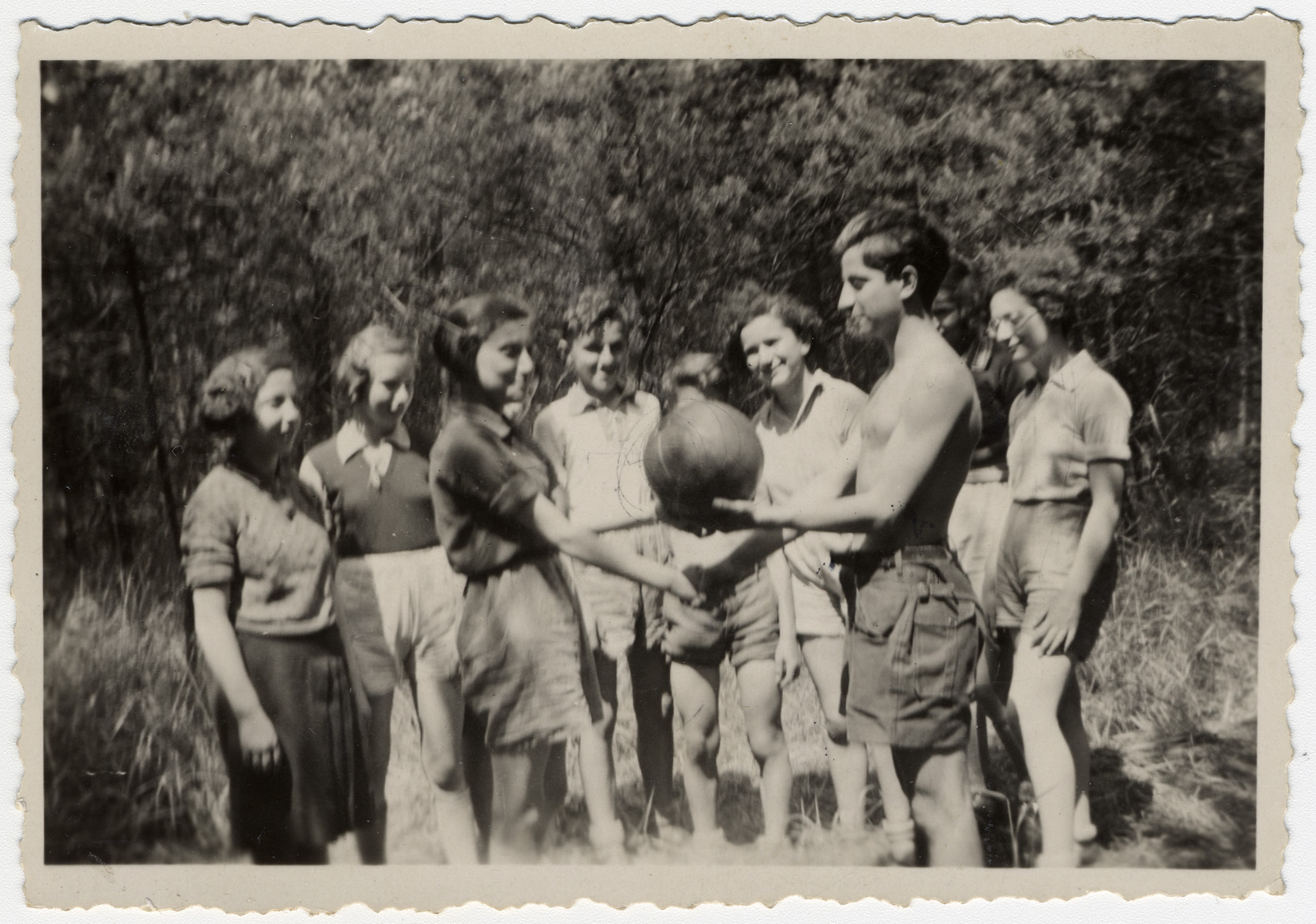 """Ruth Rappaport and a group friends from the Zionist youth group play a ball game.  The original caption in both Hebrew and German reads: """"On the route to freedon, ball sanctification."""""""
