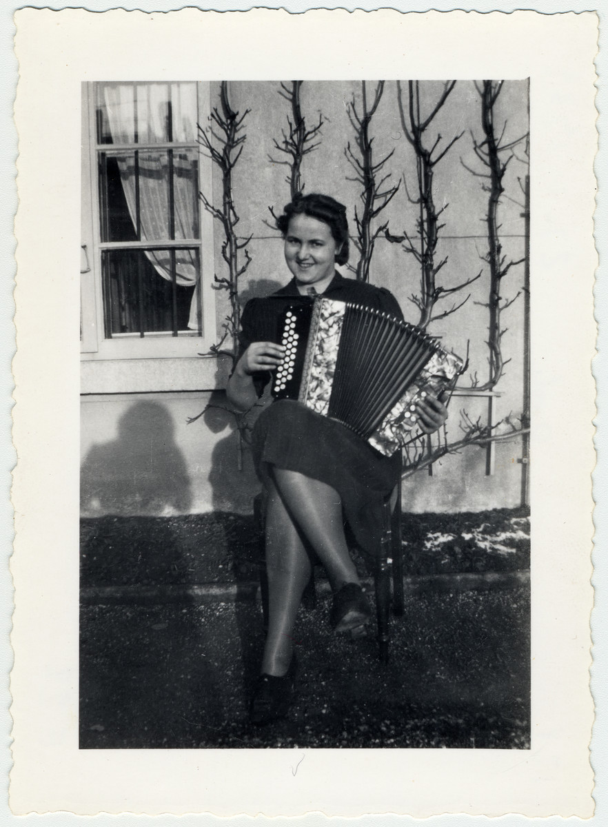 Gret Luley sits outside a building in the Herzog's garden playing the accordion.
