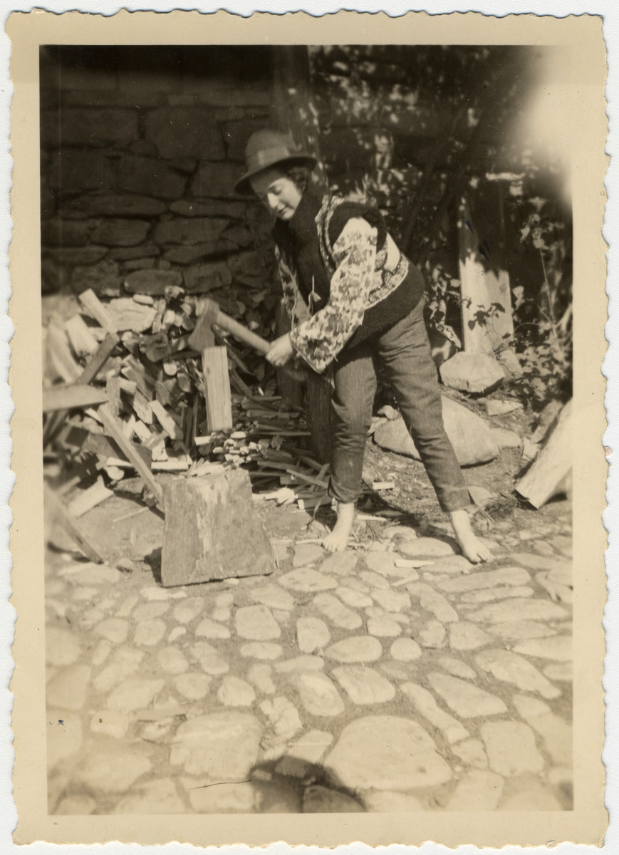 A young woman chops wood with an axe during a class trip to Tresenwald.