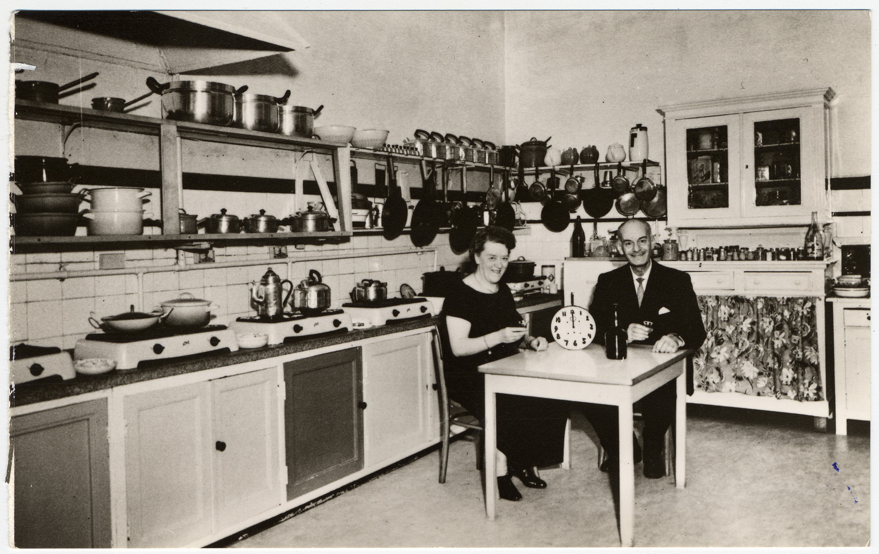 Simon and Elvire Mendels sit in the kitchen of the Hotel de Aardbol in Amsterdam.    Elvire not Jewish and kept working as the owner of the hotel during WWII. She and Simon divorced at the beginning of the war to protect her. He spent the war in hiding in the hotel itself. They remarried after the war.