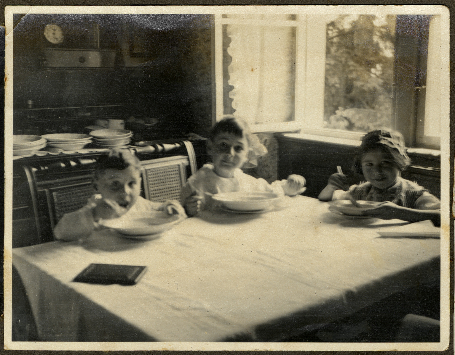 Paul, Kurt and Marianne Ehrenfeld sit at a table and eat soup.