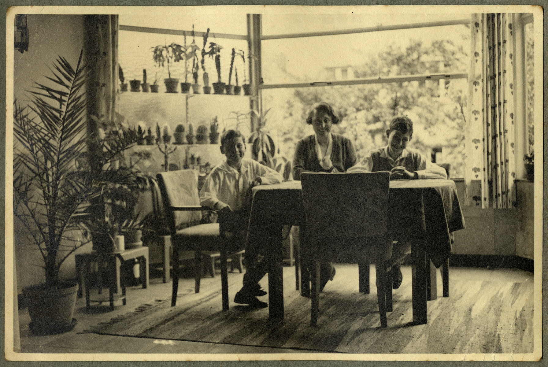 Alice Enfrenfeld sits in a sunny room filled with plants together with her two sons, Kurt (right) and Paul (left).