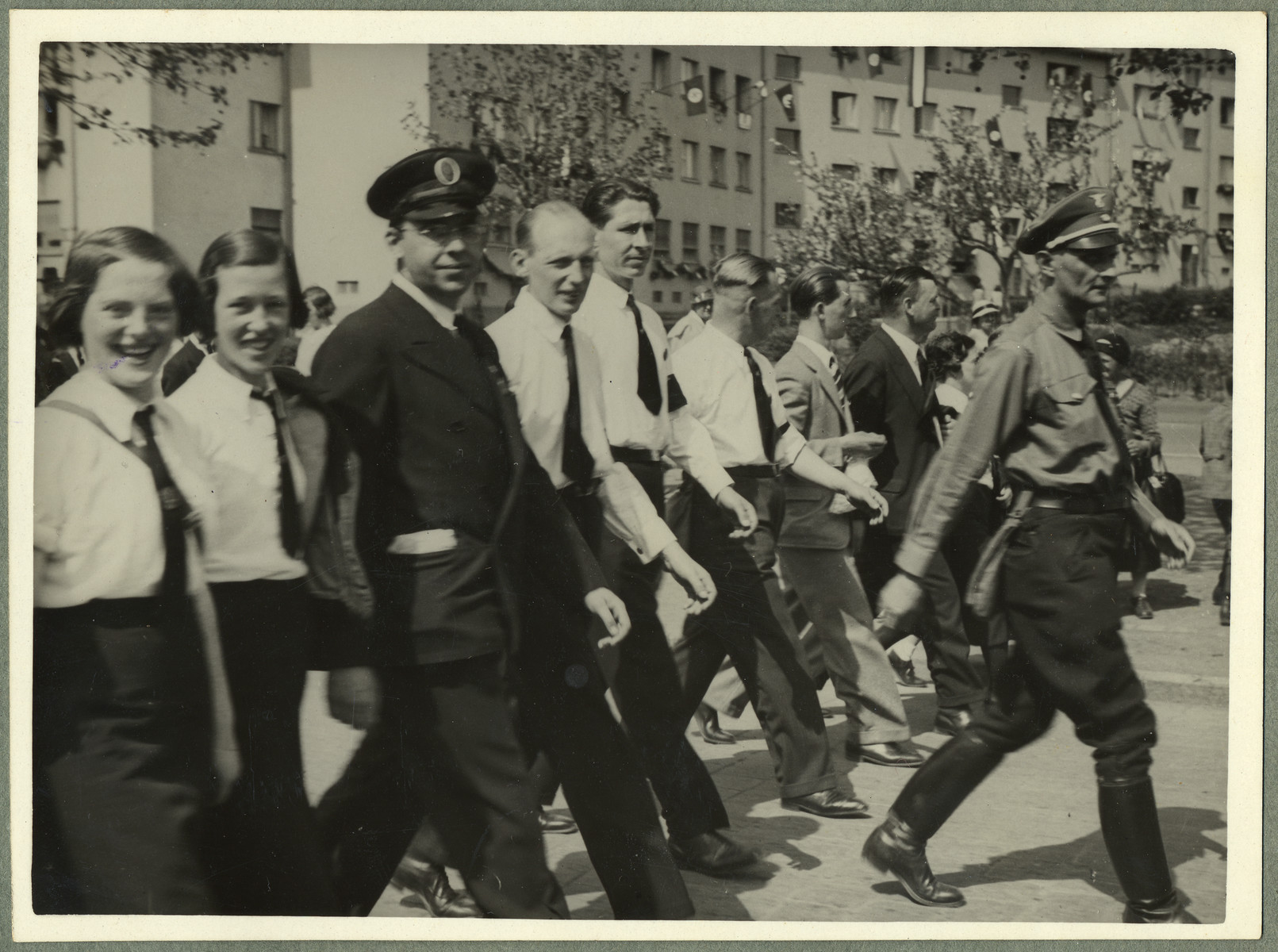 Young men and women wearing white shirts and ties march in a Nazi parade in Frankfurt.  According ot the donor, many of the men were employed by the Jewish-owned firm, Haus der Geschenke.