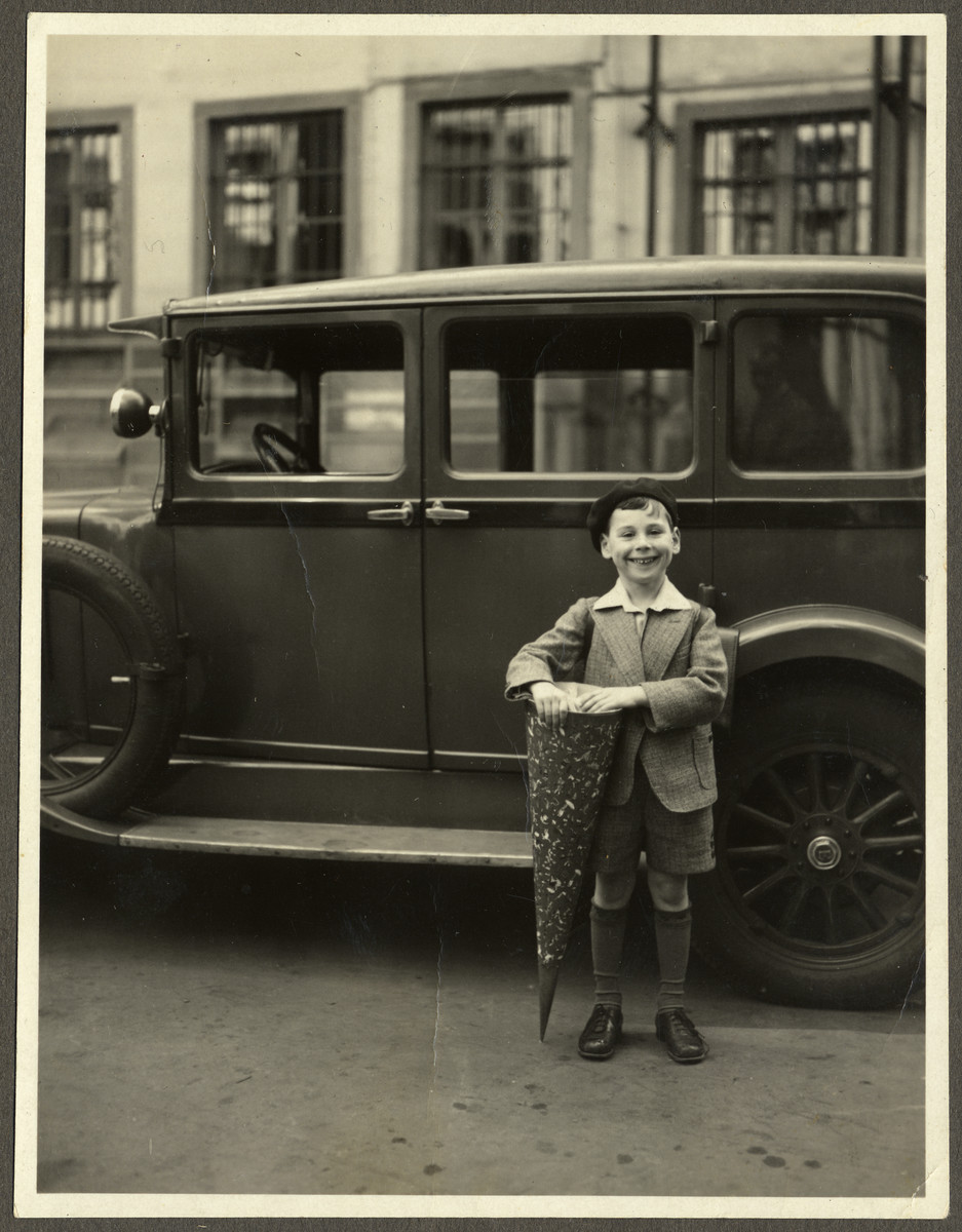 Paul Ehrenfeld poses by an automobile with a cone of sweets on his first day of school.