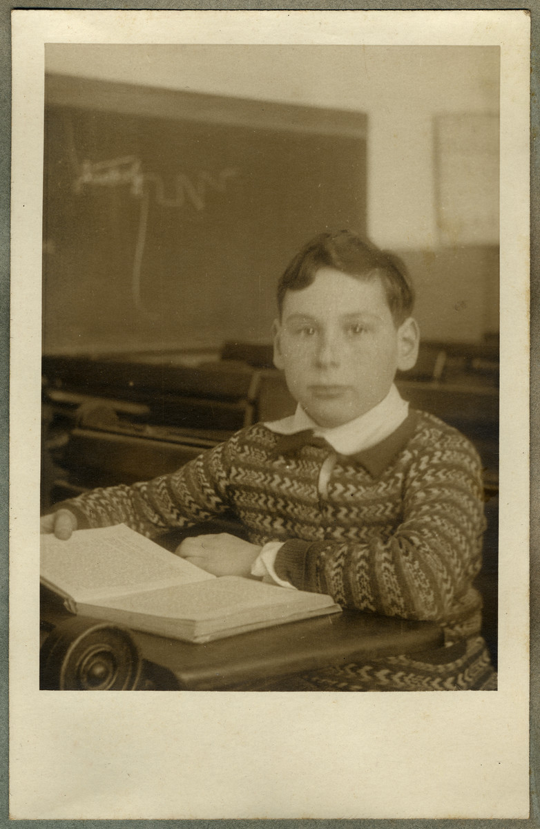 School portrait of Paul Ehrenfeld sitting at his desk reading a book.
