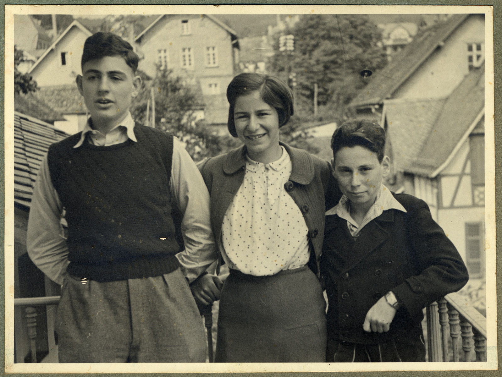 Close-up portrait of Kurt, Marianne and Paul Ehrenfeld standing on the porch of a building in Frankfurt.