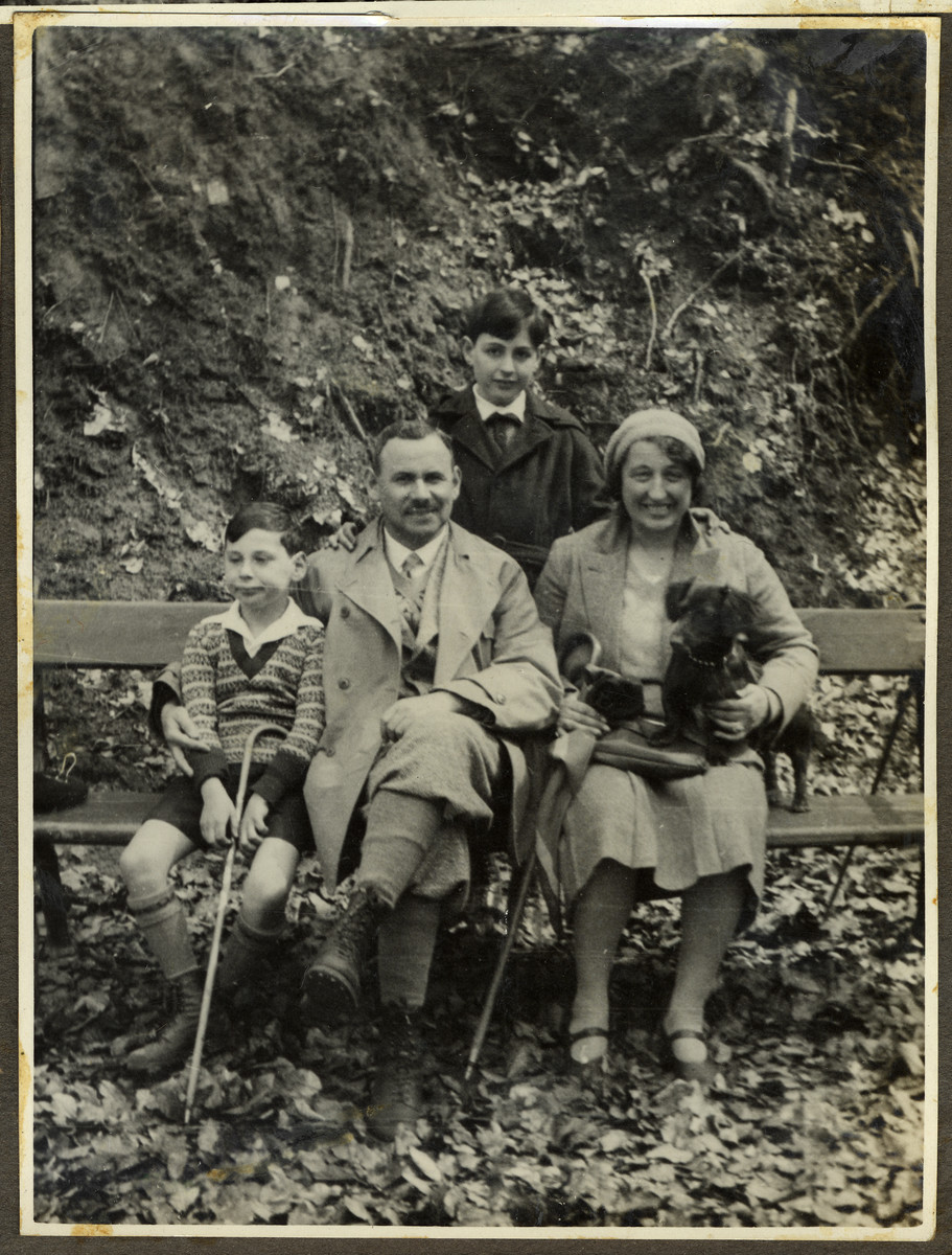 The Ehrenfeld family rests on a bench during an excursion to the woods near their summer home in Falkenstein.  From left ot right are Paul, Hans and Alice Ehrenfeld.  Standing behind them is Kurt.